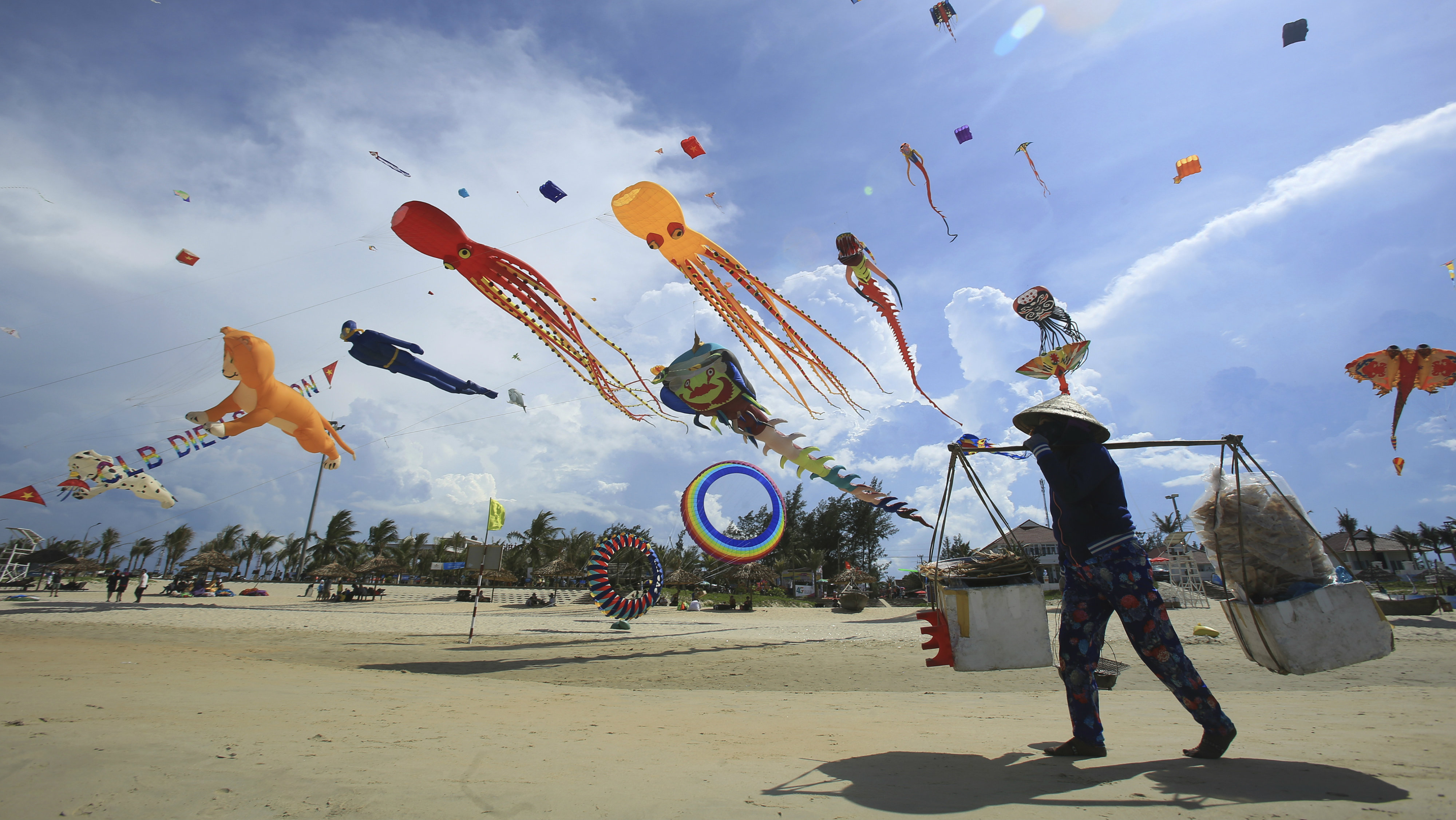 In this Sunday, June 11, 2017, photo, a food vender walks under flying kites on Tam Thanh beach during an International Kite Festival in Quang Nam province, Vietnam. Hundreds of flying giant sea creatures, animal shaped and folklore inspired kites from 20 countries were taken to the sky.