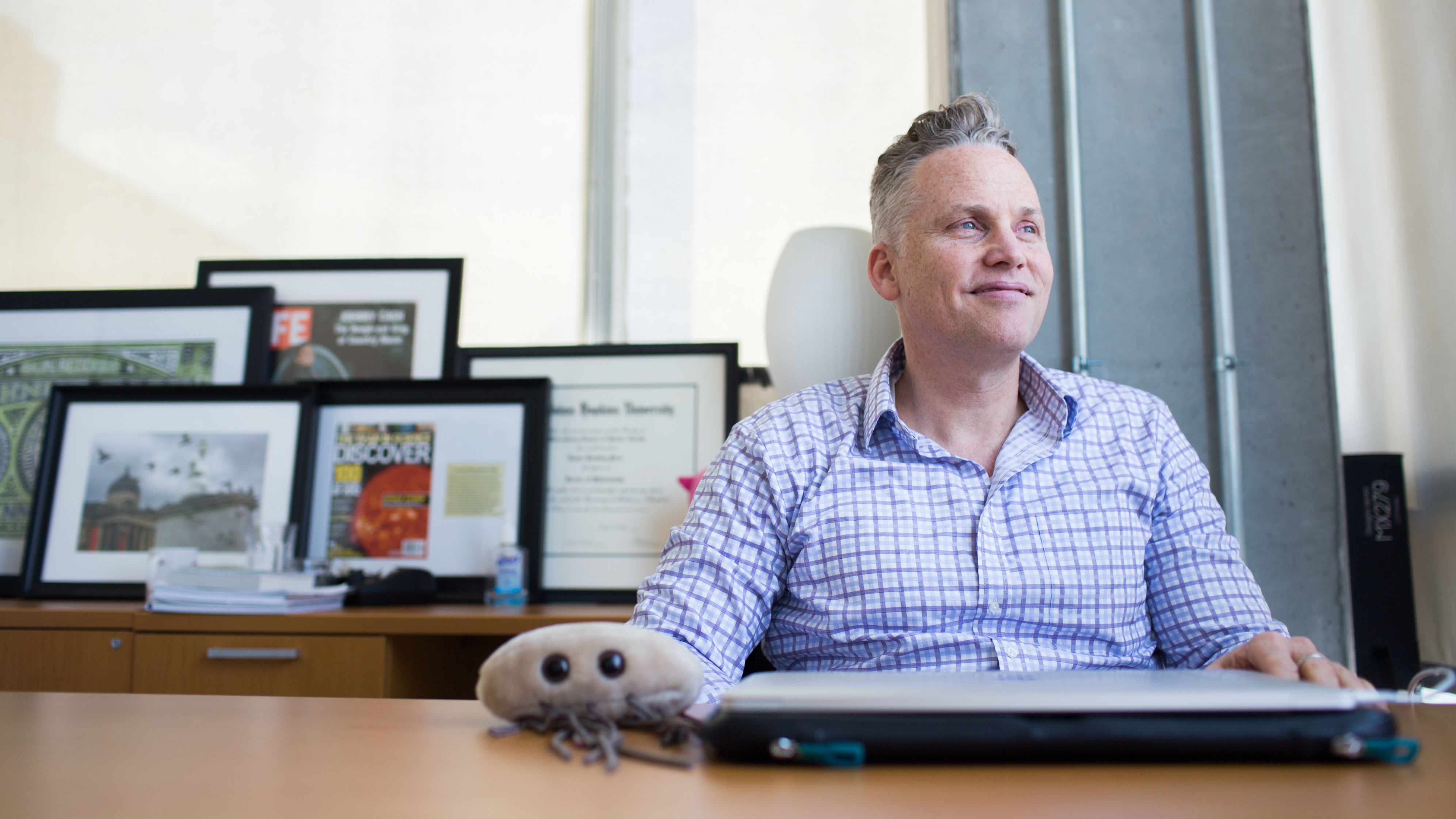 Lance Price sits at his desk with a plush E. coli