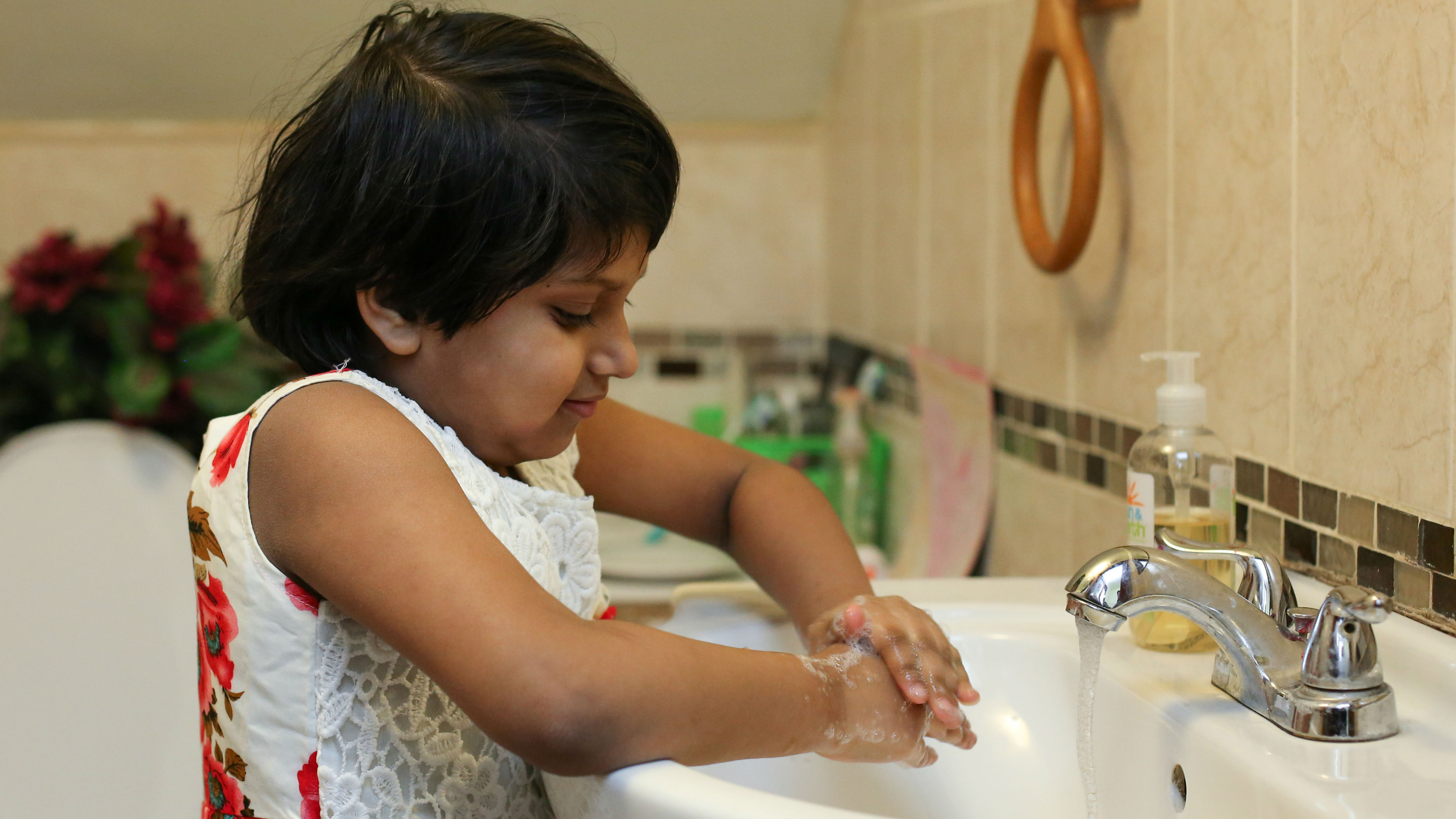 A girl washing her hands in a sink.