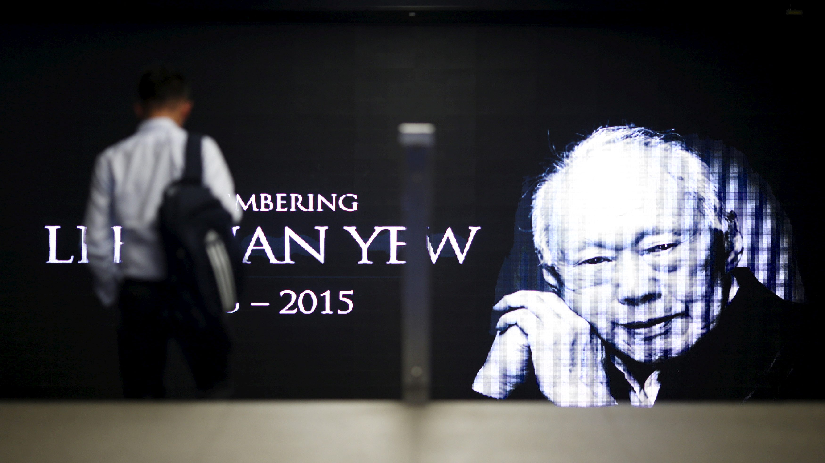A commuter passes by a signboard bearing an image of the late first prime minister Lee Kuan Yew in a train station at the central business district in Singapore