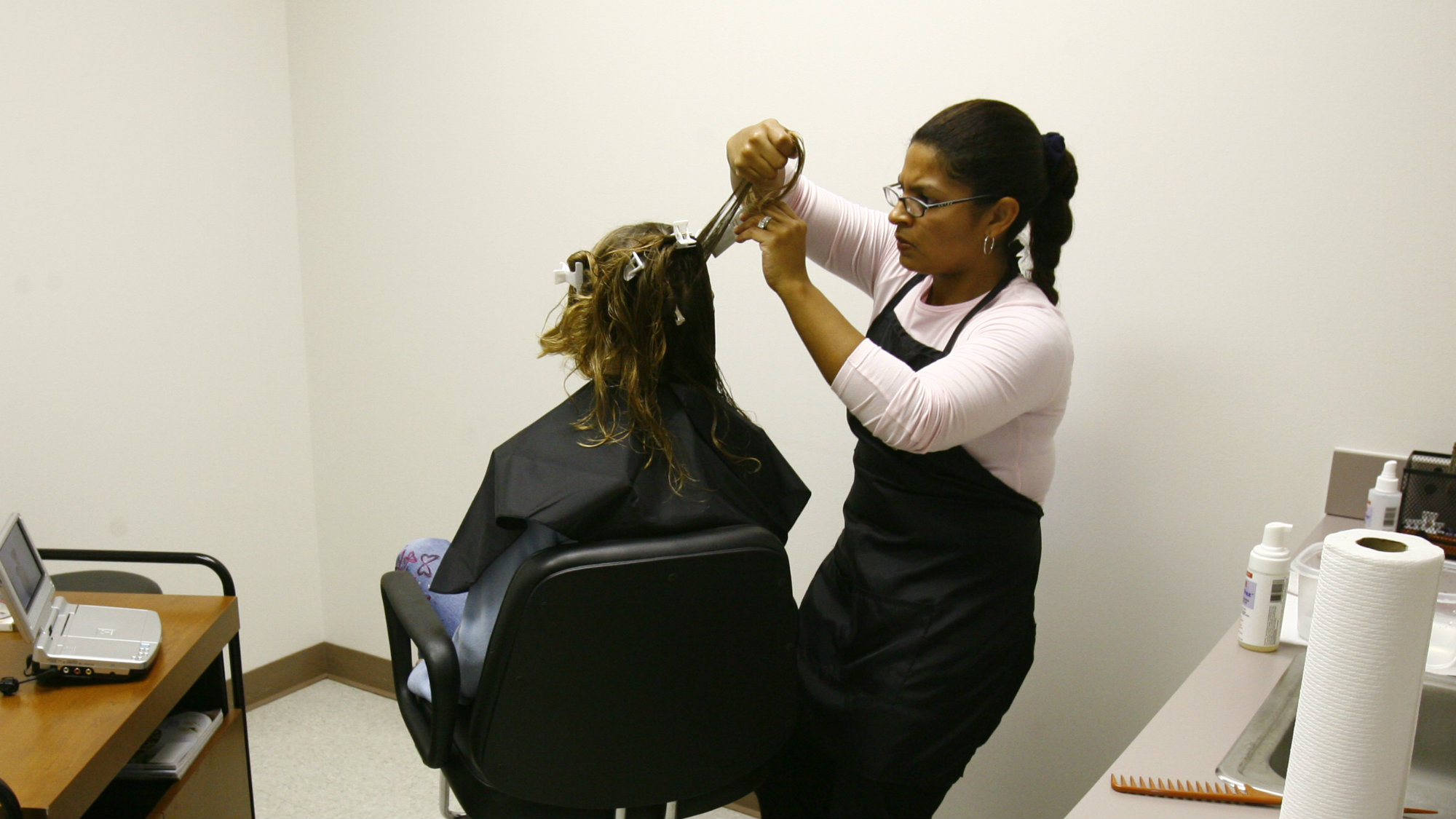Chante Ballou, right, a licensed vocational nurse with The Texas Lice Squad, looks for lice on a client Friday, Oct. 26, 2007, Missouri City.