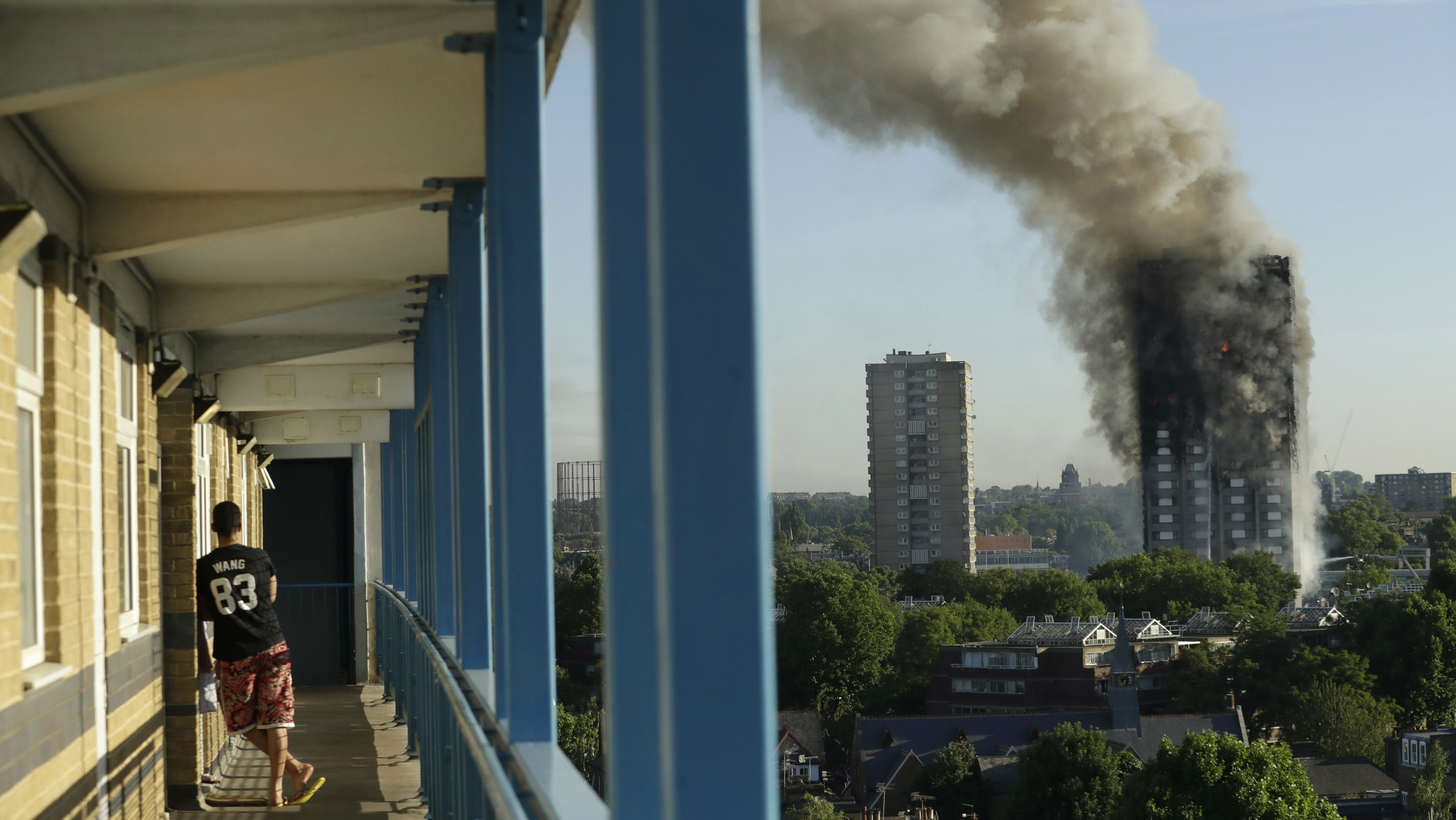 A resident in a nearby building watches smoke rise from a building on fire in London, Wednesday, June 14, 2017. A massive fire raced through the 27-story high-rise apartment building in west London early Wednesday, sending at least 30 people to hospitals, emergency officials said.