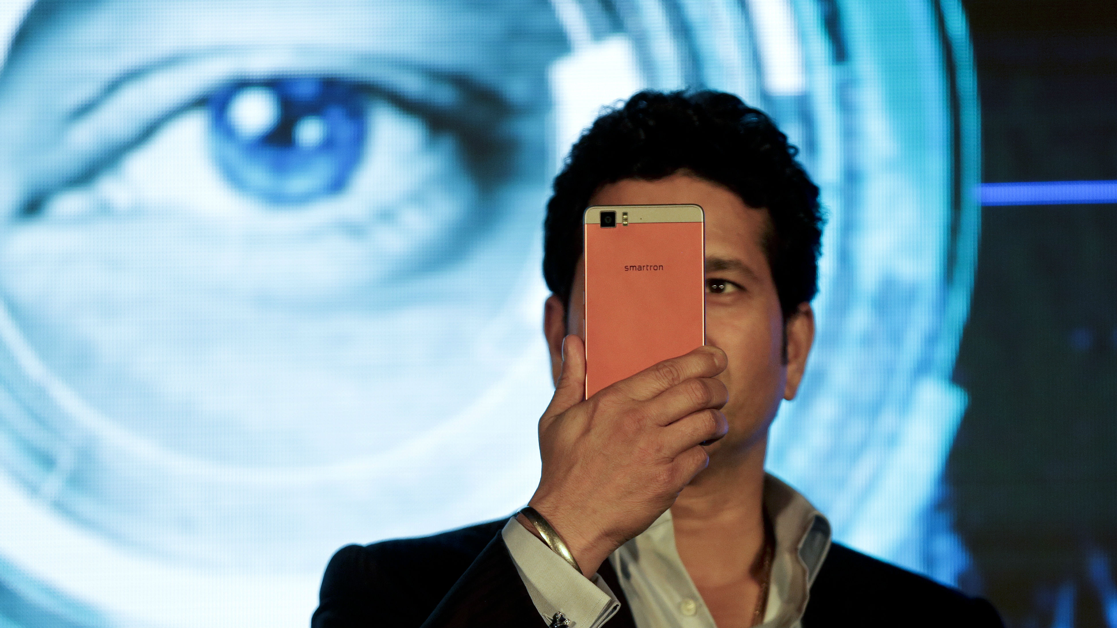 Former Indian cricketer Sachin Tendulkar scans his iris with a t.phone smartphone manufactured by Smartron, India's global technology OEM Company, during its launch in New Delhi, India, Thursday, March 31, 2016.