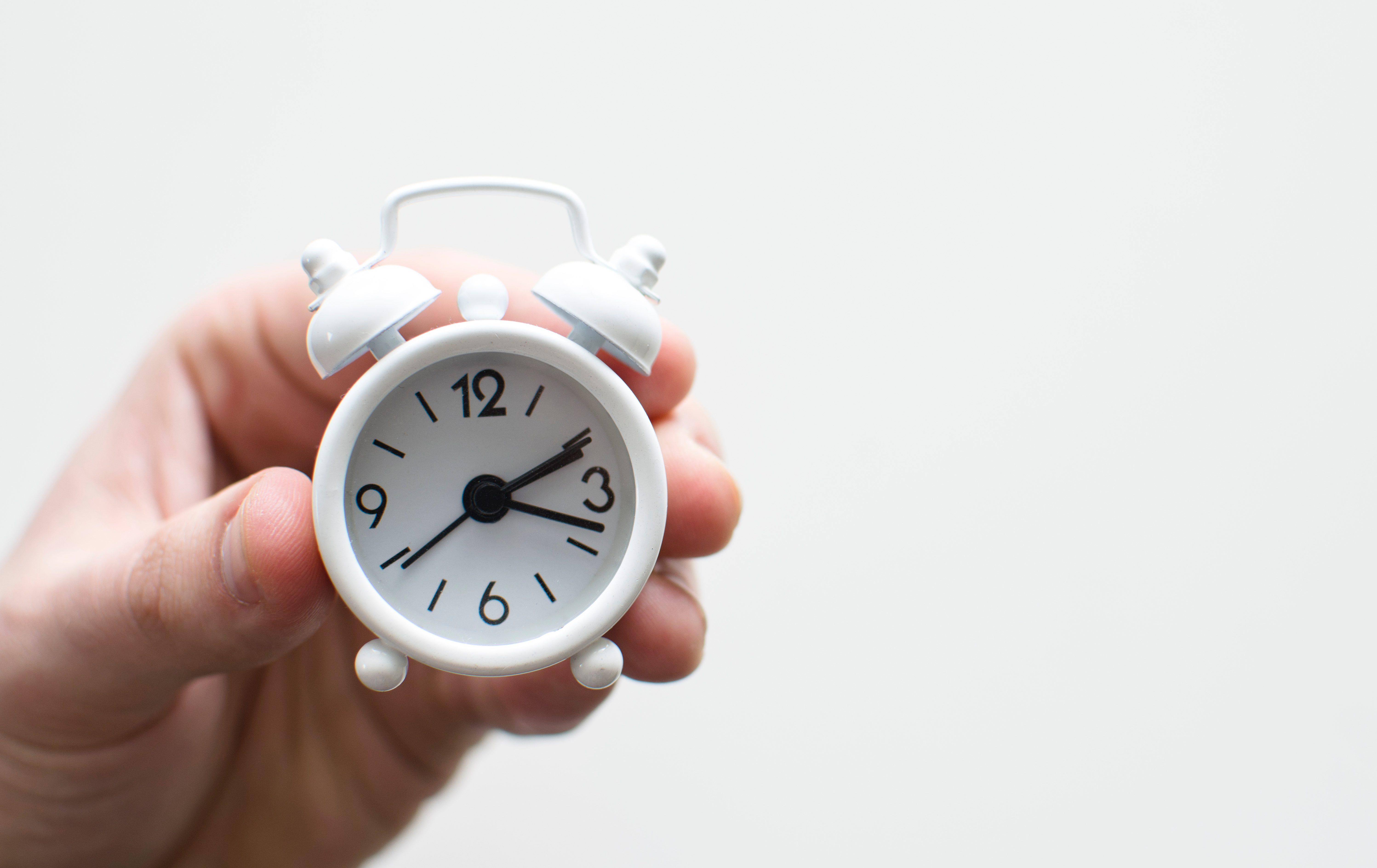 A hand holds a tiny white alarm clock