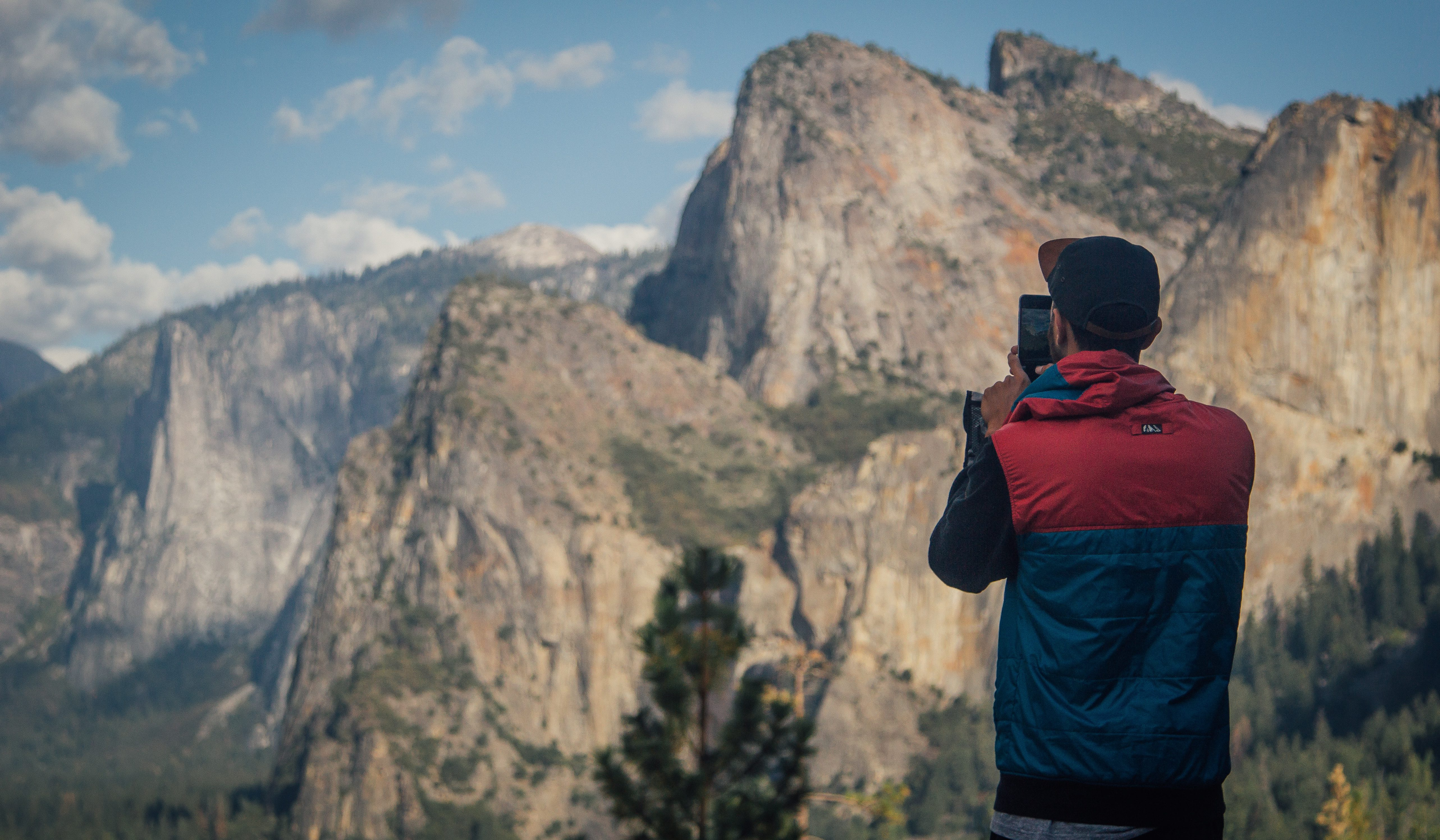 A man in a vest and baseball cap stands on the edge of a cliff taking a photo of the surrounding mountains with his iPhone.