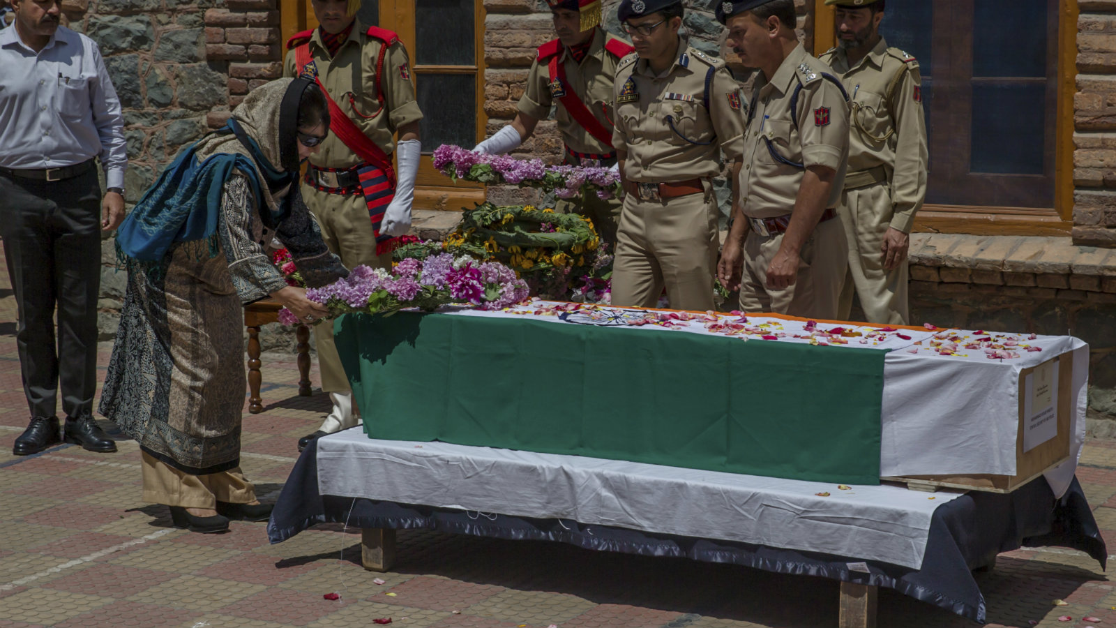 Jammu & Kashmir chief minister Mehbooba Mufti places a wreath on the coffin of Mohammad Ayub Pandit, a policeman beaten to death by a Kashmiri mob, on June 23, 2017.
