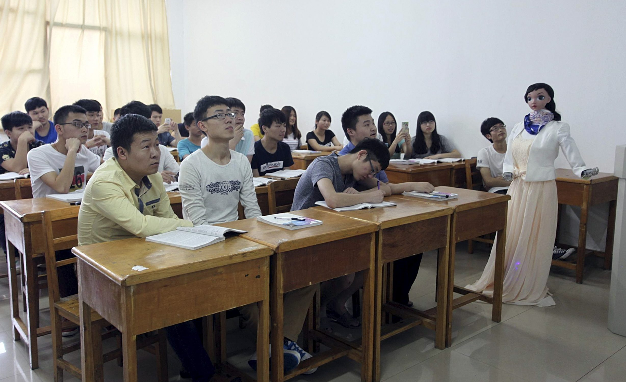"""A robot teacher named """"Xiaomei"""" (R) gestures during a demonstration at a class of Jiujiang University, in Jiujiang, Jiangxi province, China, June 3, 2015. The robot, designed and made by a team led by teacher Zhang Guangshun, is able to narrate the teaching materials and response to several voice orders like """"repeat"""" or """"continue"""". It took the team a month time to build the robot, local media reported. Picture taken June 3, 2015. REUTERS/China Daily"""