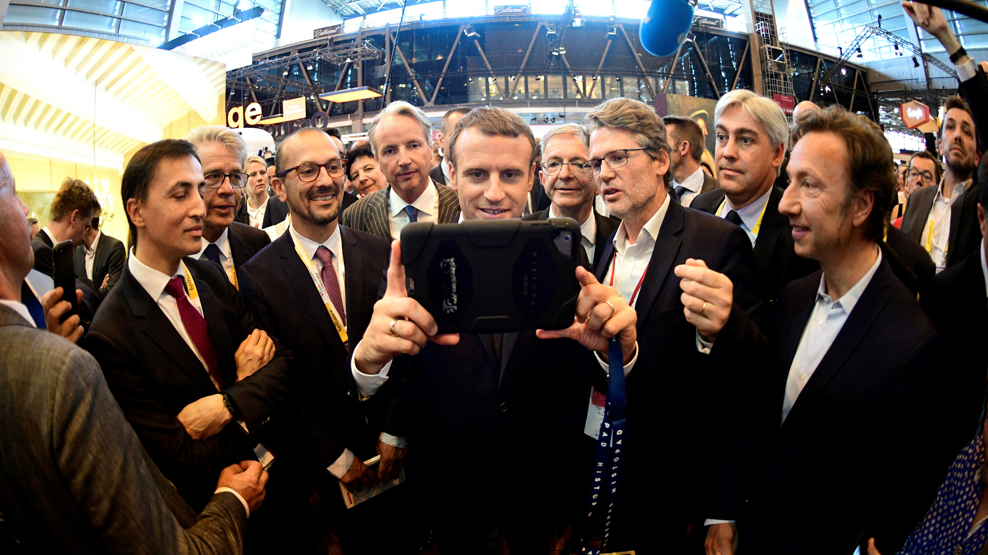 French President Emmanuel Macron (C) holds a device at the Viva Technology event dedicated to start-ups development, innovation and digital technology in Paris, France, June 15, 2017.