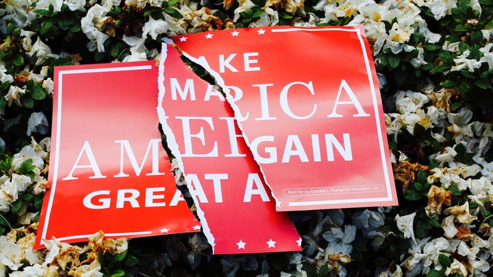 Male America Great Again torn sign.