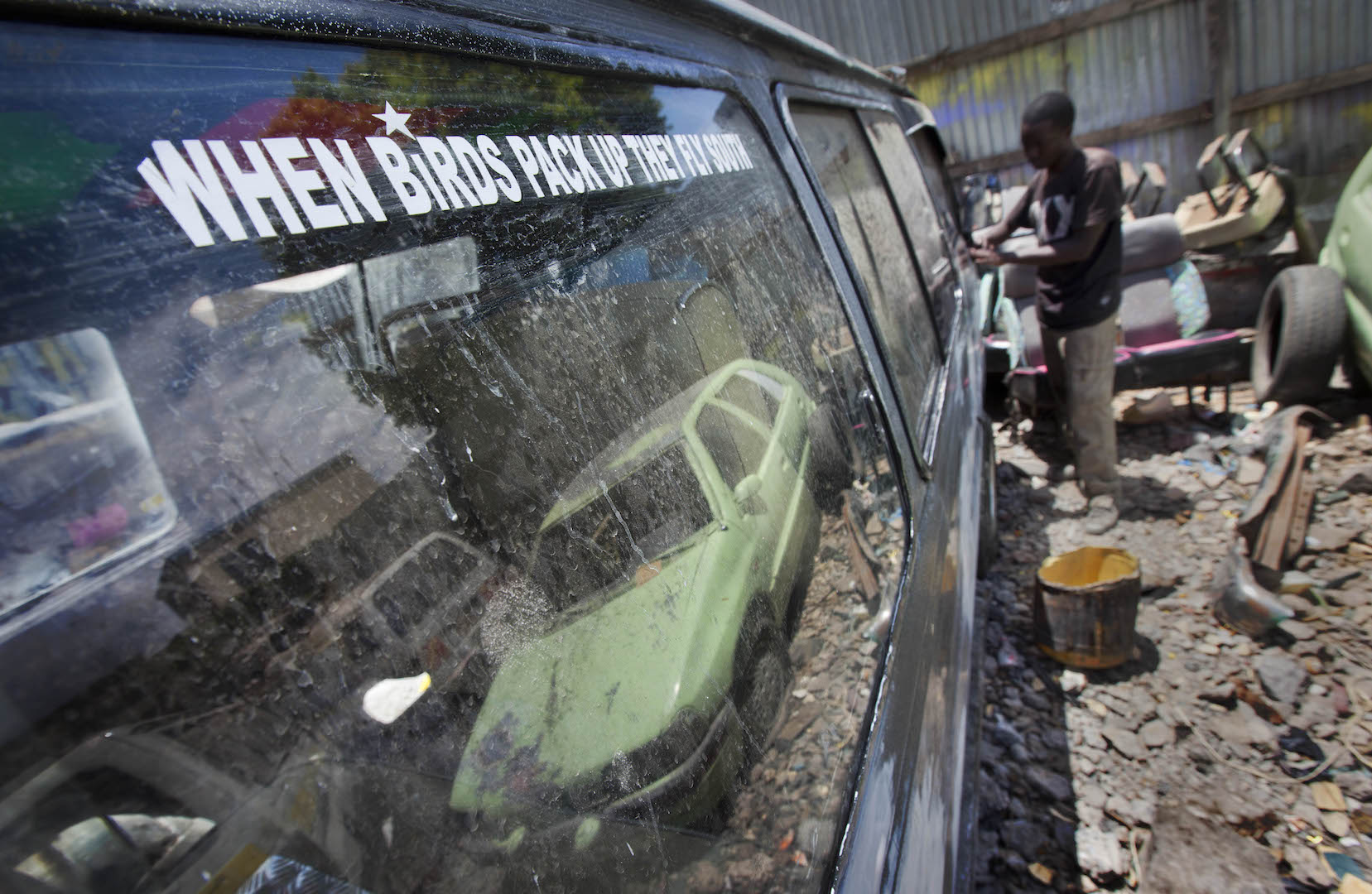 A painter strips paintwork and decals from a matatu or minibus-taxi at the Moha Graphics bodyshop in the Eastleigh area of Nairobi, Kenya.