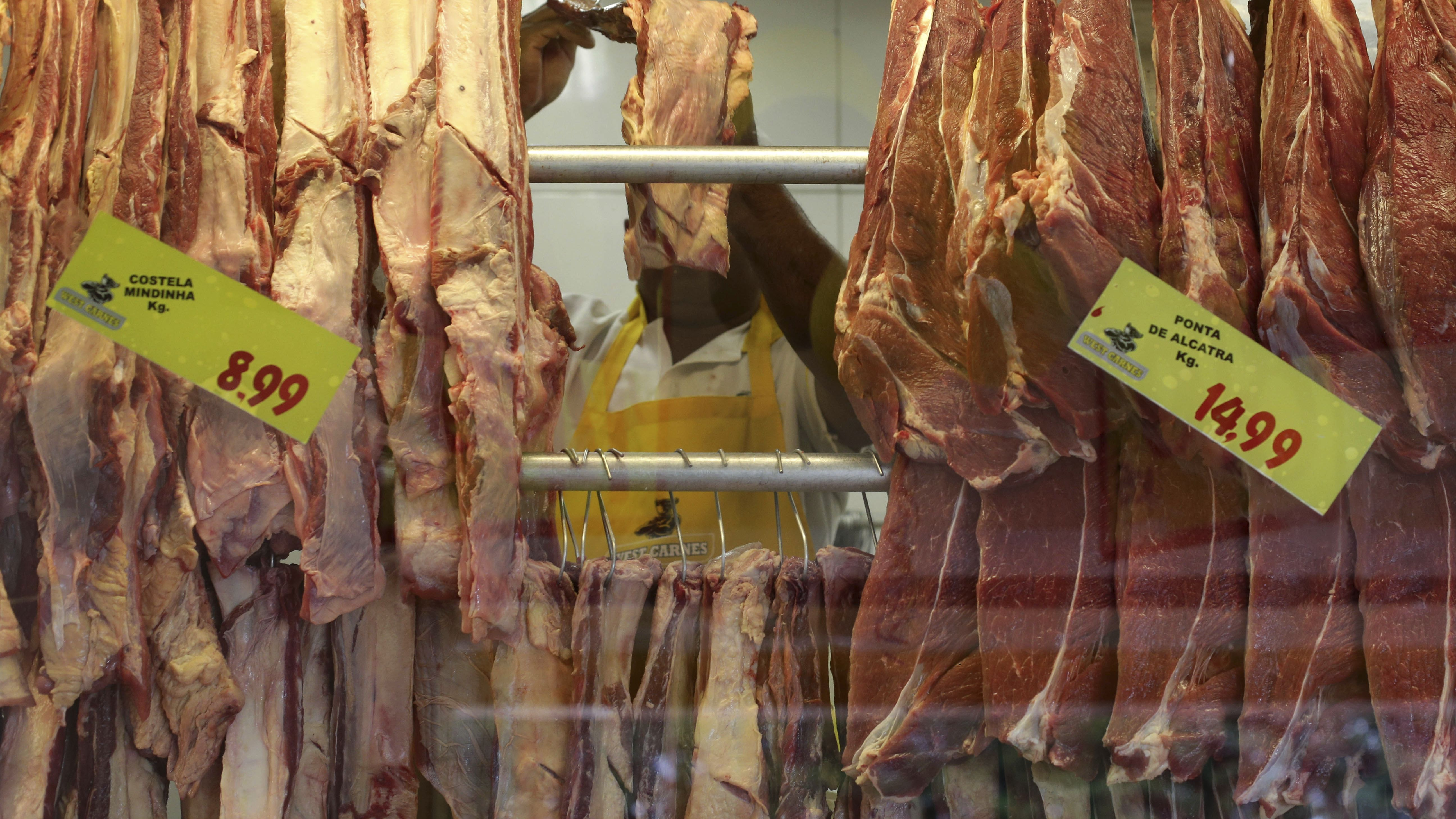 An employees works in a butcher shop in Brasilia, Brazil, Monday, March 20, 2017. The European Union's spokesman in Brazil says the union is temporarily halting some imports of Brazilian meat amid an investigation into a massive scheme of meat adulteration, which involved some of the country's largest producers.