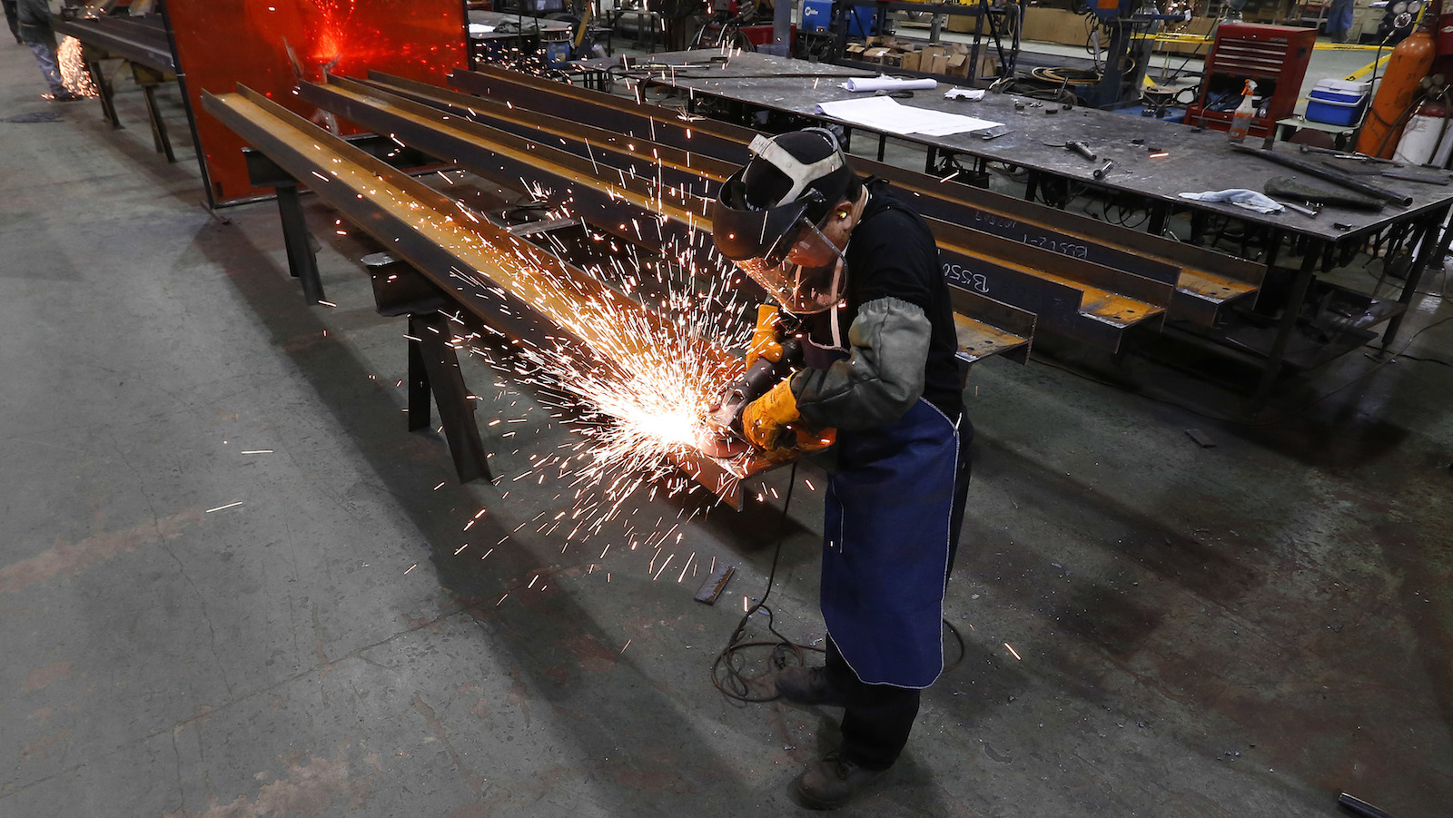 A middle-skill worker grinds steel at the IDEAL Group factory in Detroit.