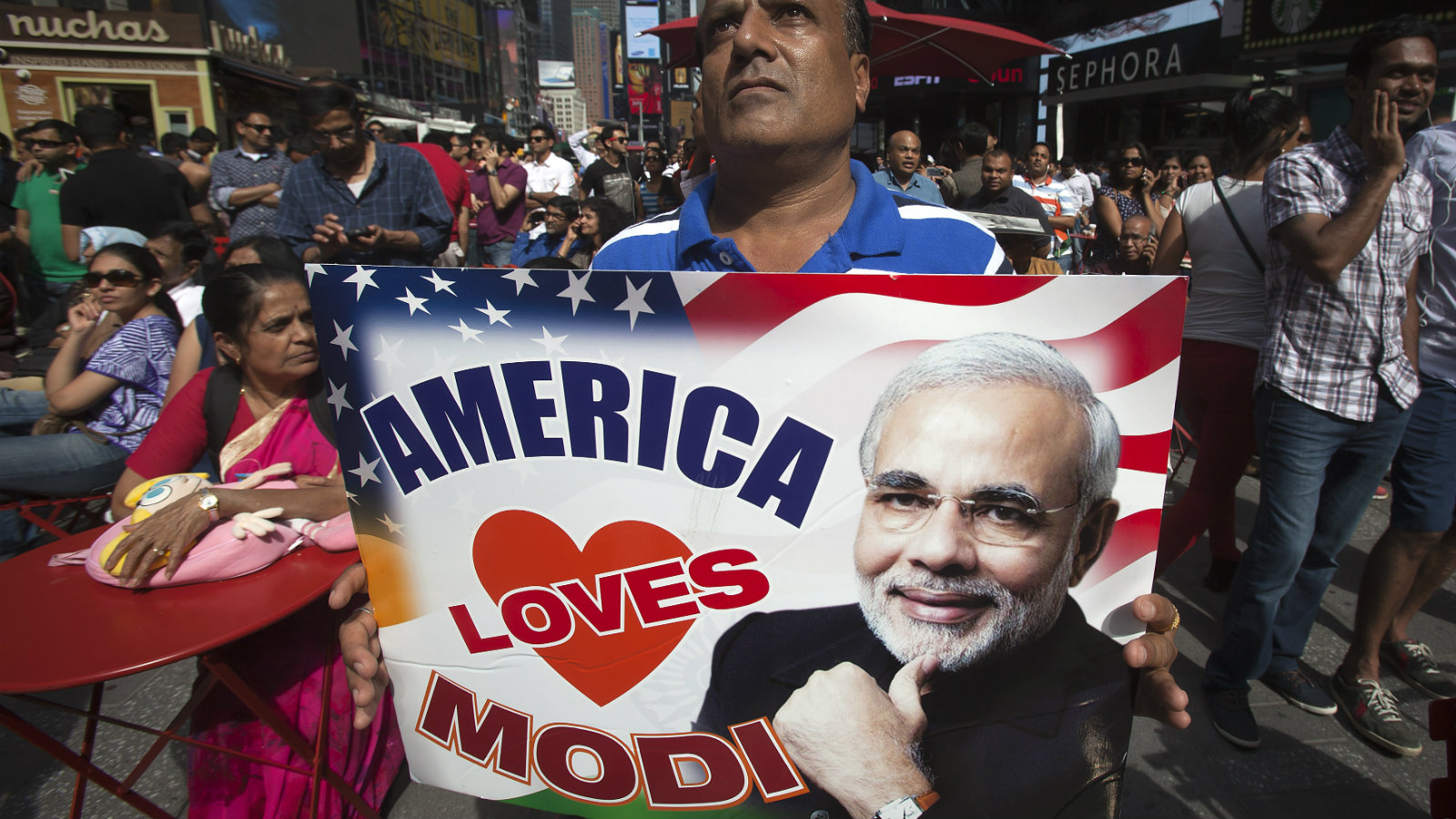 A supporter hold up an America Love Modi sign as he assembles with a large crowd of people in Times Square to watch the speech by India's Prime Minister Narendra Modi simulcast on a giant screen in New York September 28, 2014.