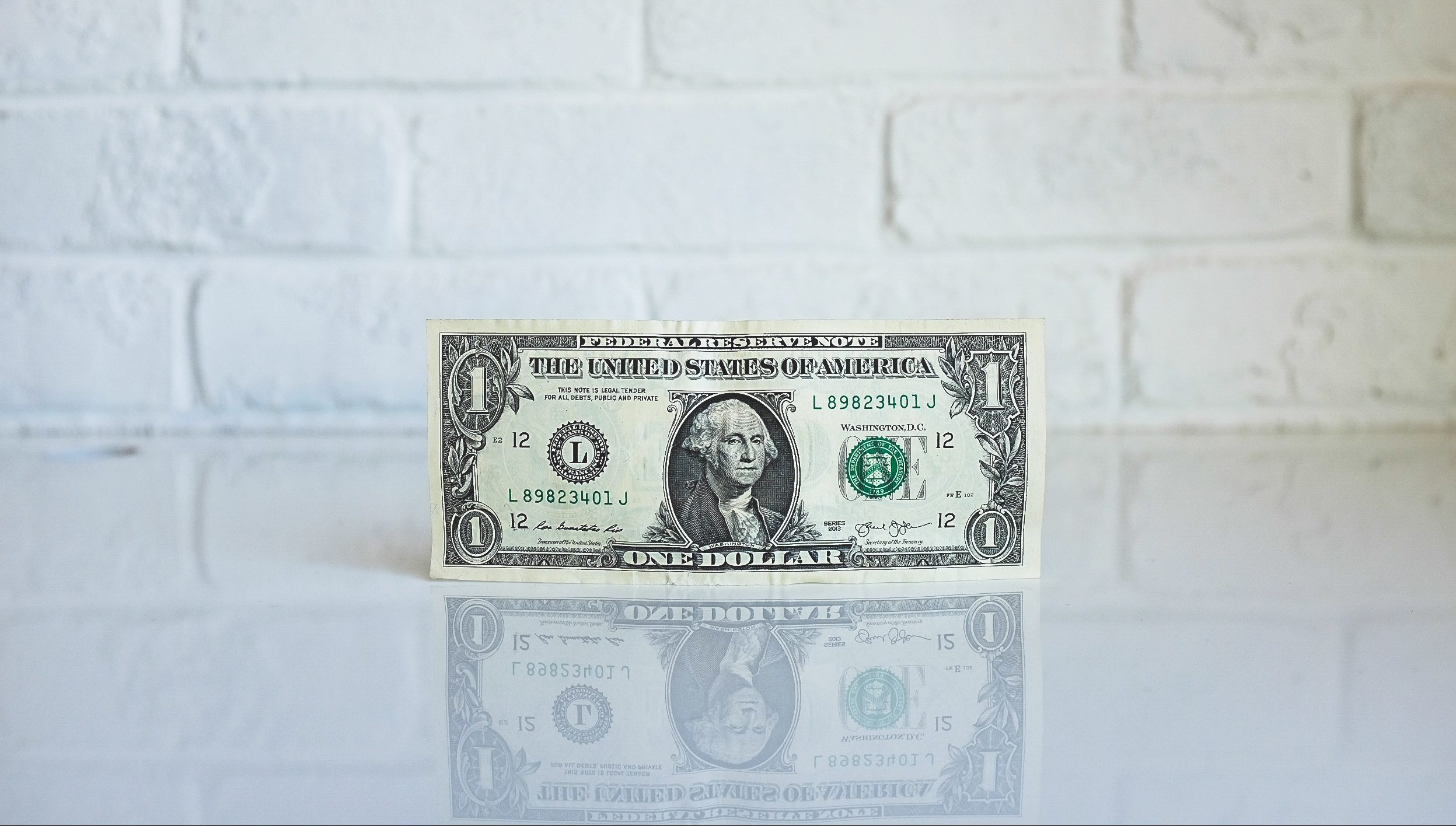 A dollar bill stands on a white table against a white wall