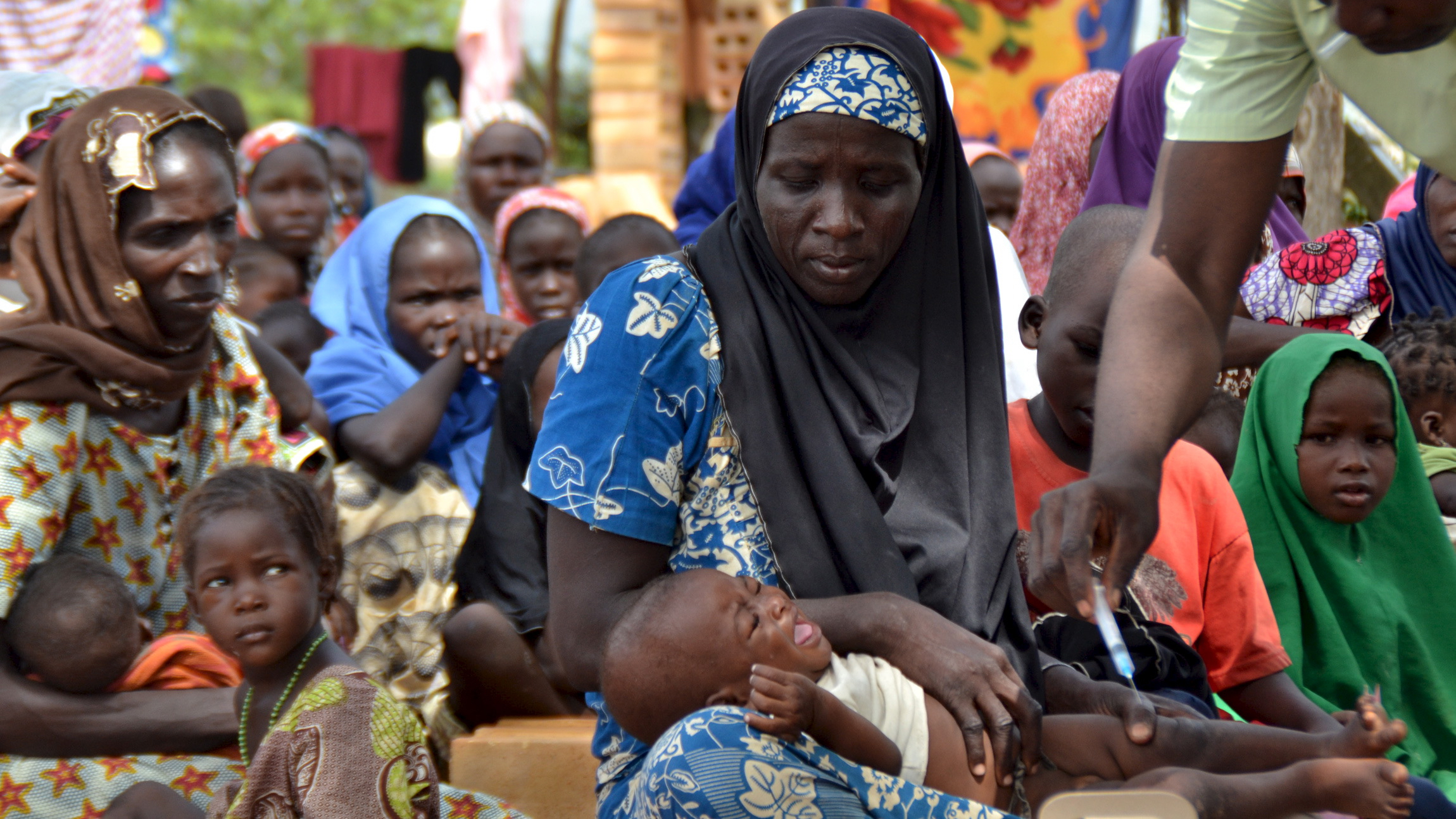 A woman carries her baby as a paramedic official administers an injection at an internal displaced person's camp, after they were rescued with other abductees from Boko Haram, near Mubi, northeast Nigeria October 29, 2015. Nigeria's armed forces on Wednesday said it had rescued 338 people held captive by Boko Haram and raided a number of the Islamist militant group's camps on the edge of its stronghold in the northeast's Sambisa forest. Picture taken October 29, 2015. REUTERS/Stringer - RTX1TX8Y