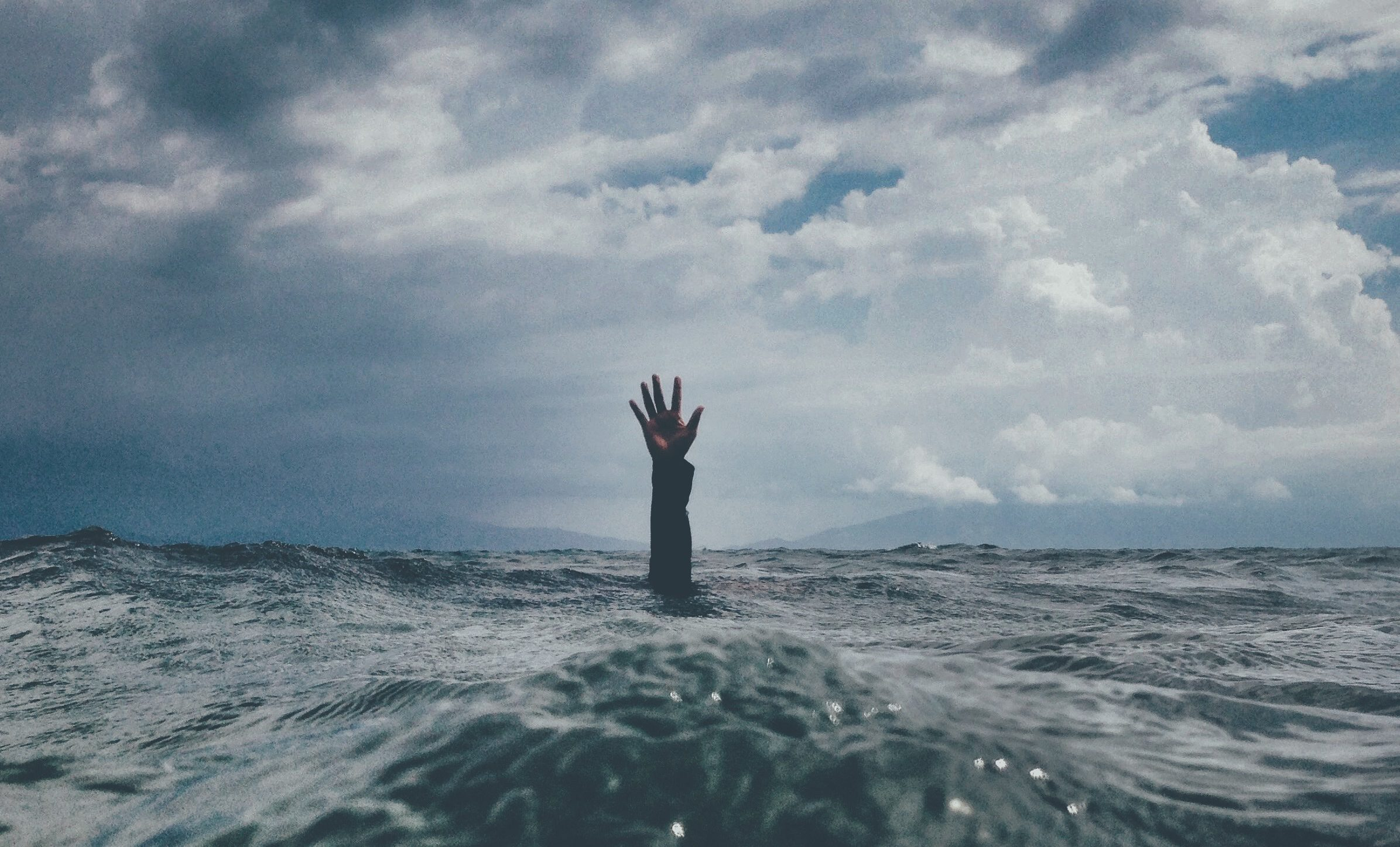 A person is entirely submerged under water with only one arm breaking through and reaching straight up.