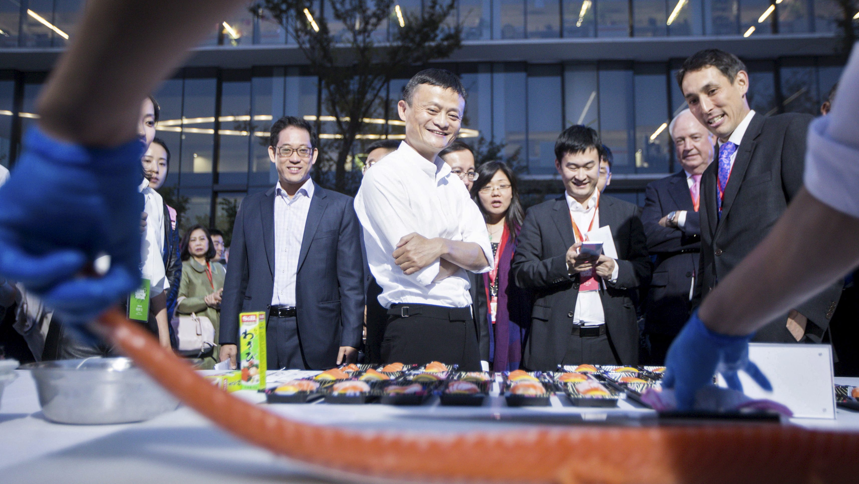 Alibaba Group's executive chairman Jack Ma (C) looks on as a chef prepares to slice salmon at a display area for fresh food ingredient vendors, who recently signed a cooperation agreement with Alibaba's Tmall, after the launch event of Tmall 11.11 Global Shopping Festival, at the company's headquarters in Hangzhou, Zhejiang province, China, October 13, 2015. REUTERS/Stringer CHINA OUT. NO COMMERCIAL OR EDITORIAL SALES IN CHINA. - RTS49DX