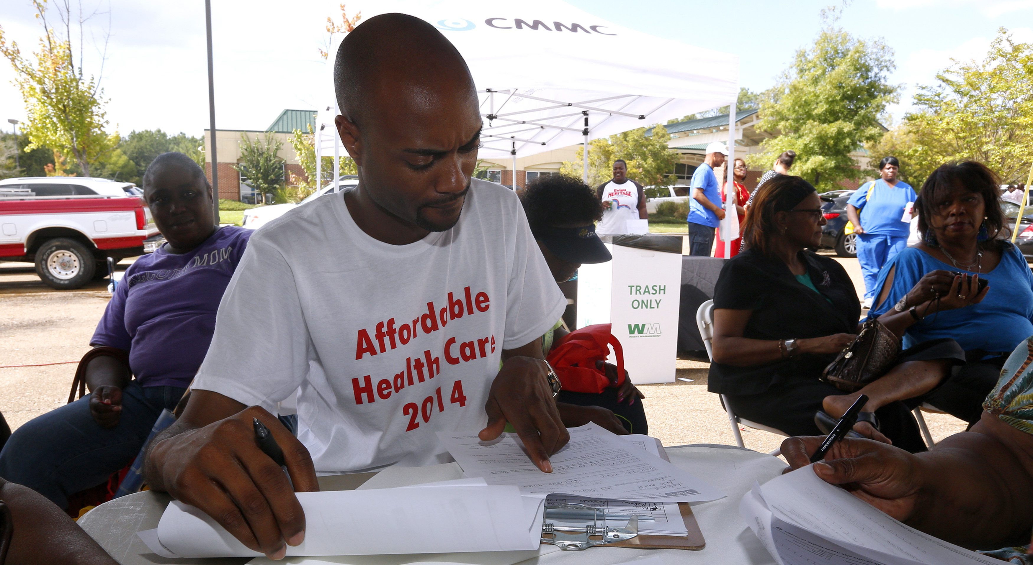 """Wilbert Jones helps local residents sign up for the Affordable Care Act, widely referred to as """"Obamacare"""", outside the Jackson-Hinds Comprehensive Health Center in Jackson, Mississippi October 4, 2013. Mississippi is one of at least 20 states that has decided not to expand Medicaid under the Affordable Care Act.   REUTERS/Jonathan Bachman  (UNITED STATES - Tags: HEALTH POLITICS BUSINESS) - RTR3FLYR"""