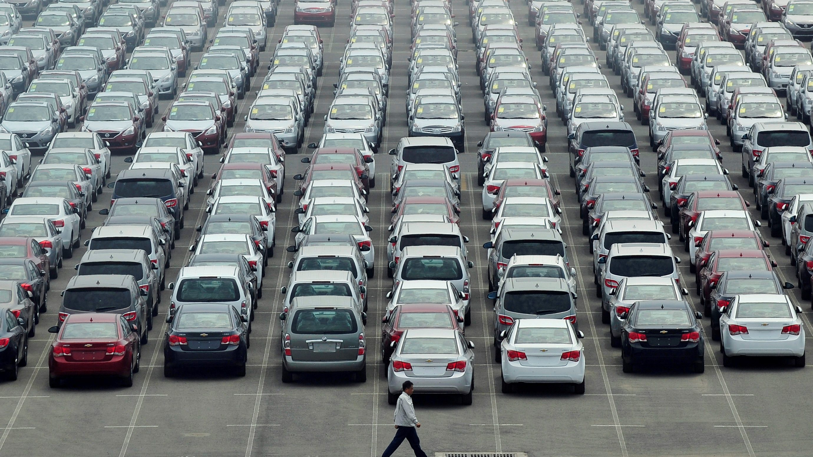 A man walks past a parking lot at Dayaowan port of Dalian, Liaoning province June 10, 2012. REUTERS/Stringer