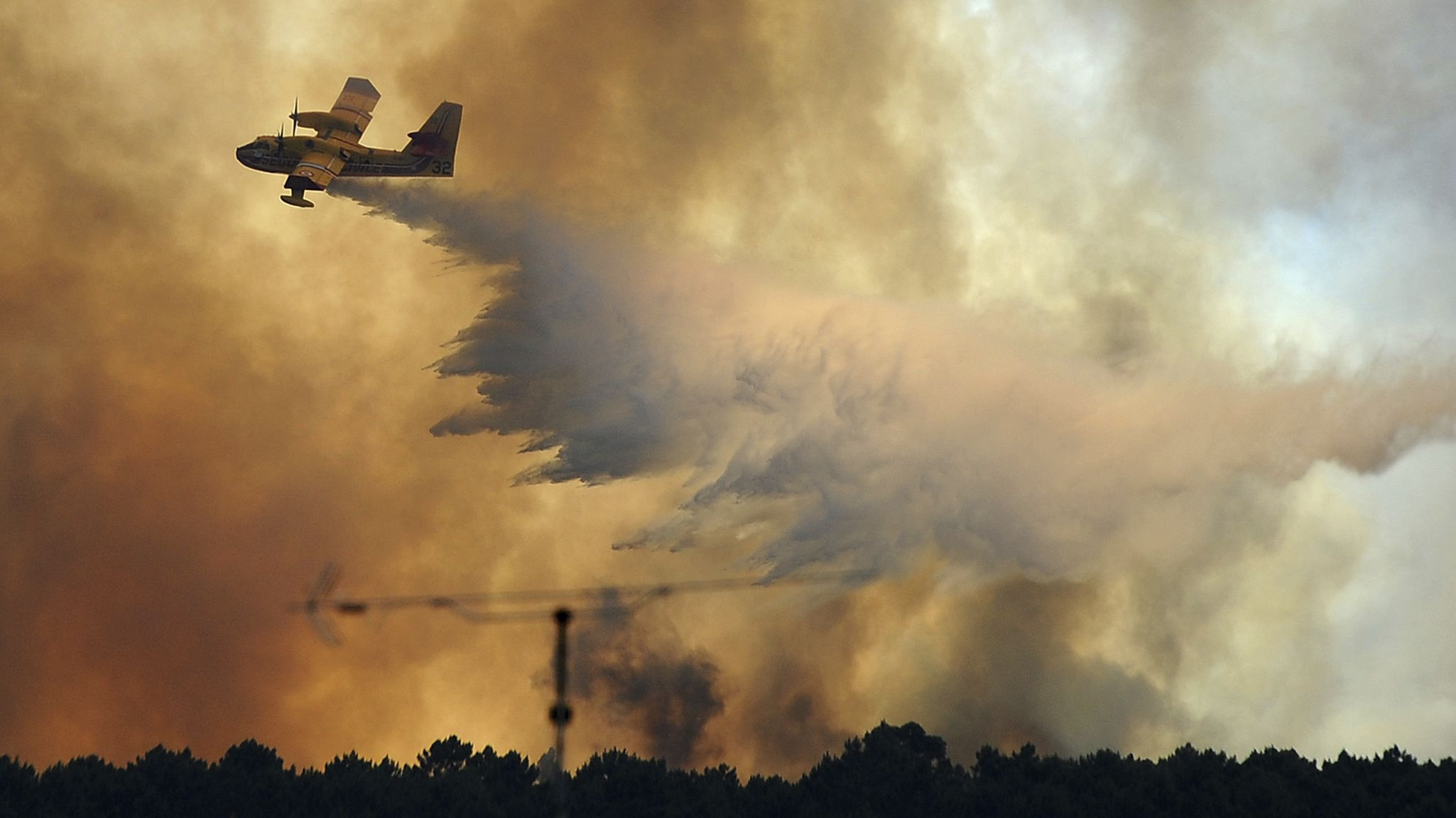 A fire fighting aircraft drops water over a fire outside the village of Pedrogao Grande central Portugal, Monday, June 19, 2017. More than 2,000 firefighters in Portugal battled Monday to contain major wildfires in the central region of the country, where one blaze killed dozens of people, while authorities came under mounting criticism for not doing more to prevent the tragedy.