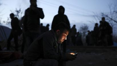 A stranded migrant checks his smart phone for news