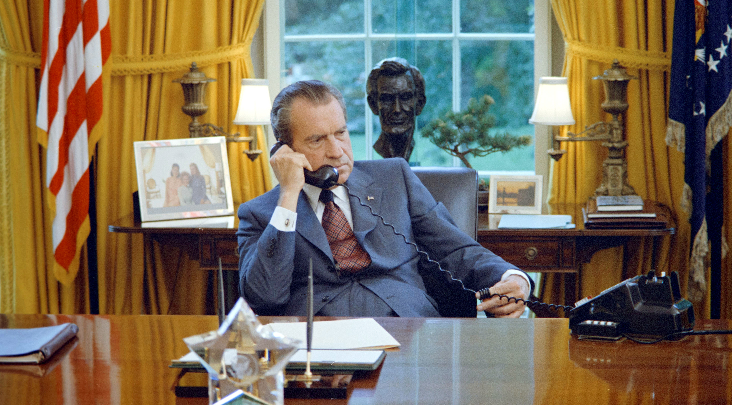 U.S. President Richard Nixon seated at his desk, with family photos and the Lincoln bust statuette visible behind him, in the White House Oval Office in Washington, U.S. on June 23, 1972.