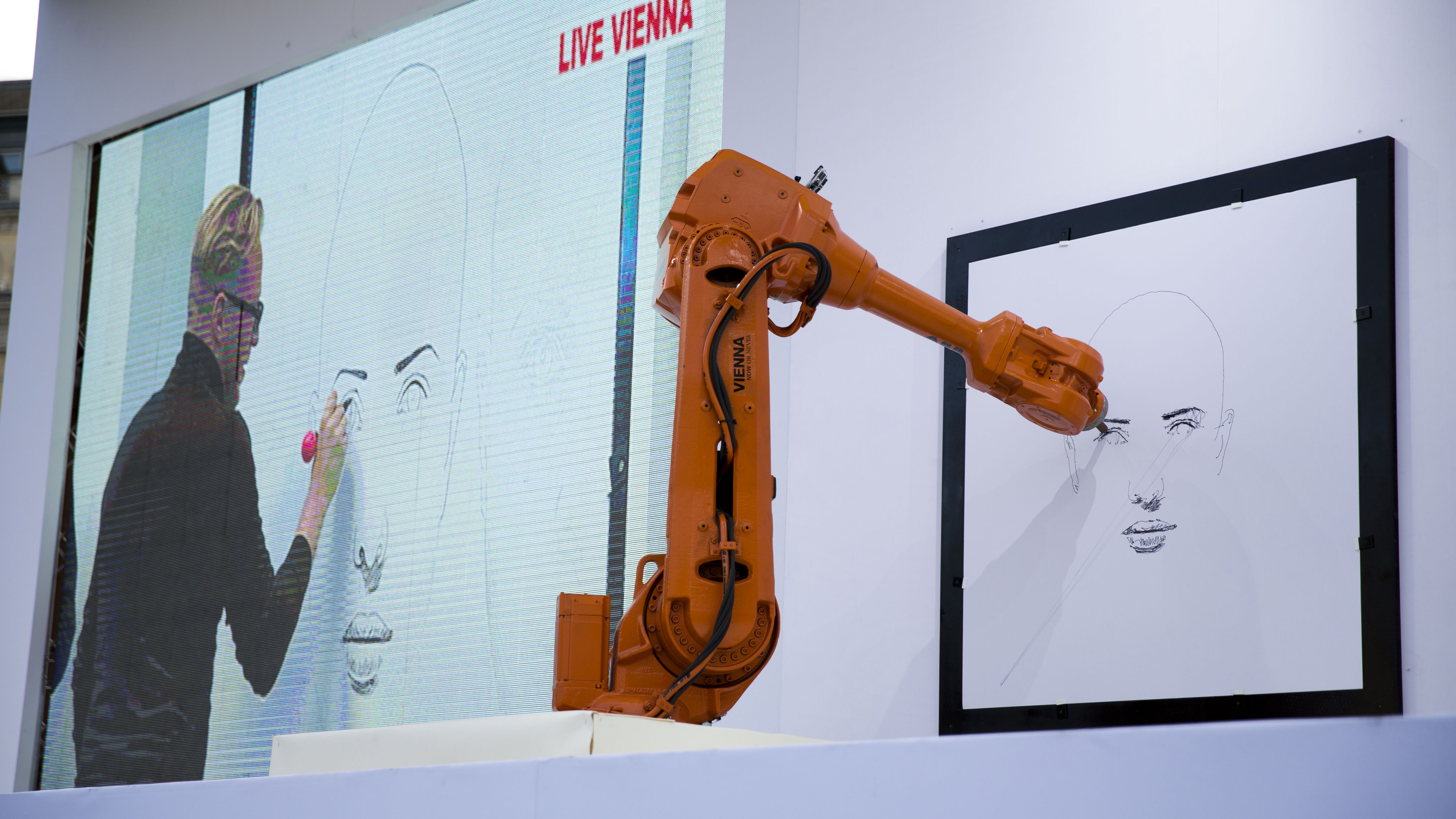 Austrian artist Alex Kiessling is shown working on a drawing live from Vienna on a big screen in Trafalgar Square, London, as robot arms in London, right, and Berlin replicate his work.