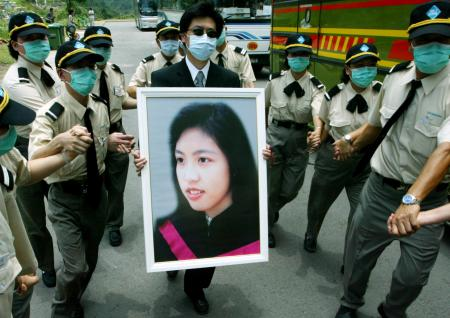 A portrait of 35-year-old doctor Tse Yuen-man who died from SARS virus is carried during her funeral in Hong Kong May 22, 2003. Tse, the first front-line doctor to be killed by the disease in the territory, was given the highest honours at her funeral and was buried in Gallant Garden, a cemetary reserved for residents who perish in the line of duty. The deadly virus has infected 1,719 people and killed 255 since it swept into the congested territory.