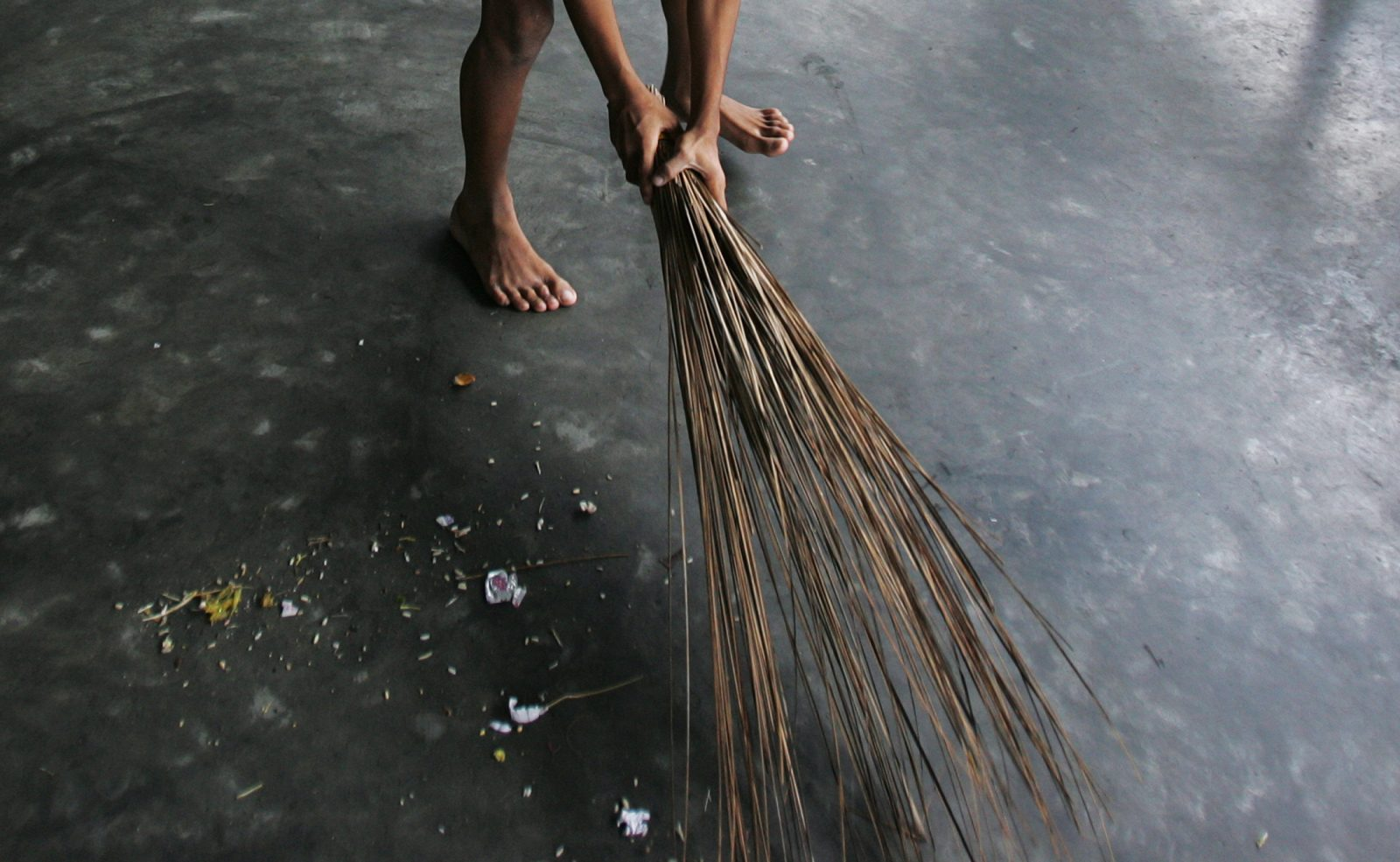 A child sweeps the floor at a rescue home run by Free the Children - India, a Non-Government Organisation (NGO), at Madhamgram village, about 25 km (16 miles) north from the eastern Indian city of Kolkata August 5, 2006. Photo taken August 5, 2006. To match feature Life India Children.