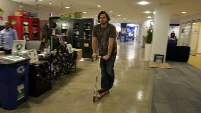 A google employee rides a scooter through Google's NY office