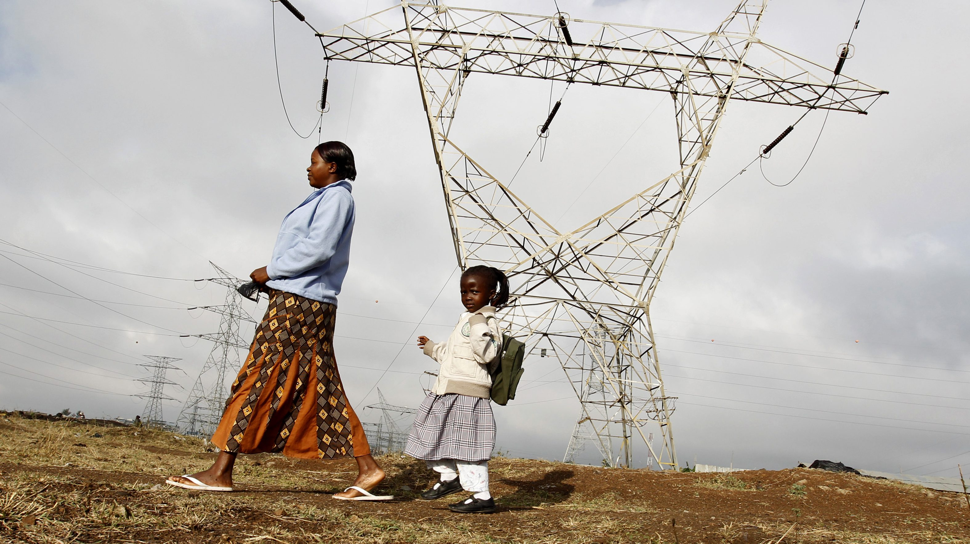A woman walks her child to school past high voltage electrical pylons on the outskirts of Kenya's capital Nairobi, March 14, 2011. A union representing workers at Kenya's sole power supplier started on Monday a strike to protest unfair employment terms, its secretary general said. Kenya power has been involved in a protracted dispute with Kenya Electrical Trade and Allied Workers Union (KETAWU), which claims that more than a third of workers are on casual terms, in violation of the country's labour law.