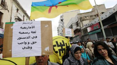 """People from Amazigh, north of Morocco, hold a Amazigh flag and a banner, as they gather for a protest in Casablanca April 24, 2011. Thousands took to the streets of Morocco on Sunday in peaceful demonstrations to demand sweeping reforms and an end to political detention, the third day of mass protests since they began in February. The banner reads, """"the Amazigh language is a statutory rightand acquired."""""""