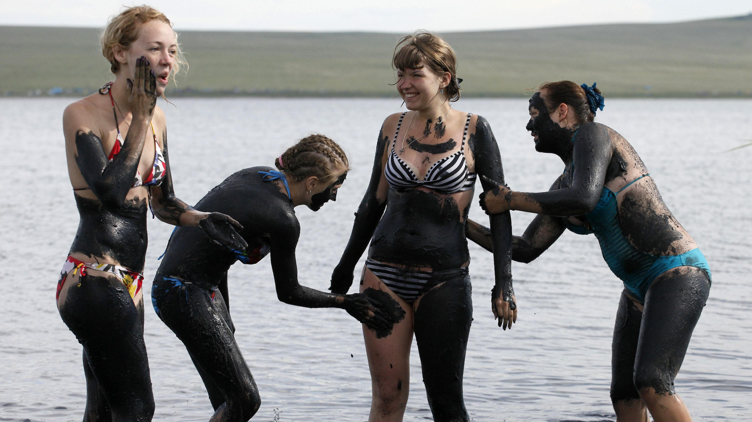 People smear each other with mineral-rich black mud in the waters of Tus lake in Russia's Khakassia region, about 370 km (230 miles) southwest of the Siberian city of Krasnoyarsk, July 15, 2011. Russians from different regions annually arrive at the Tus lake rich with curative black and blue mud to live in a camp, bathe in the bitter-salty water and smear themselves with mud, which is a healing remedy, in their opinion.