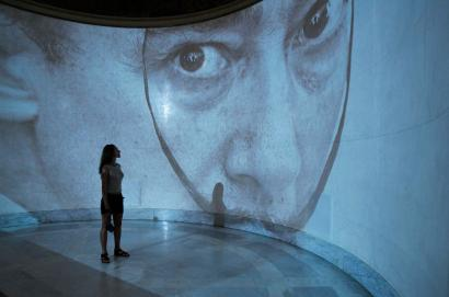 A visitor looks at a projection of Salvador Dali during a presentation of a new exhibition of his work at Moscow's Pushkin Museum