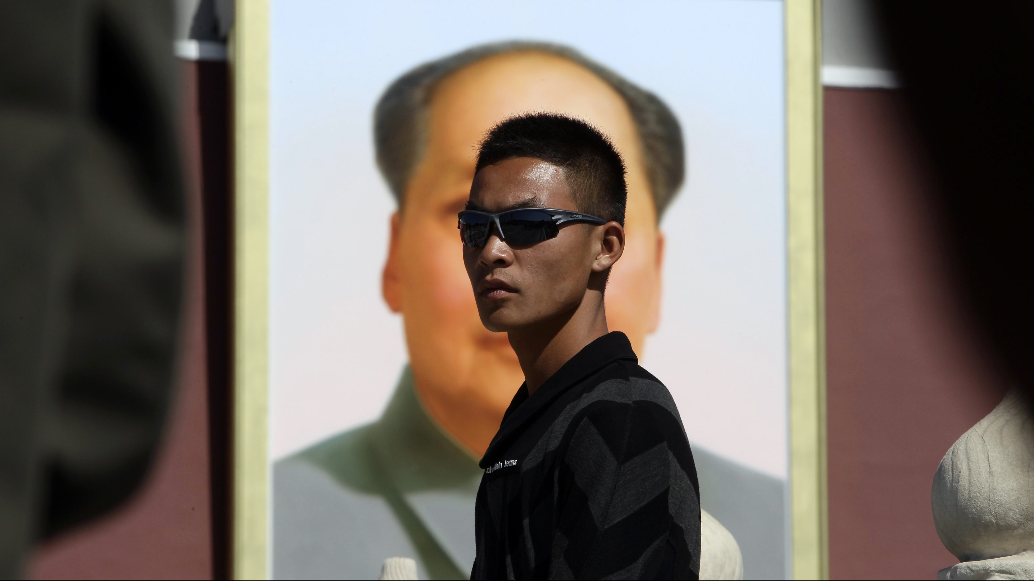 A plainclothes paramilitary policeman keeps watch in front of a portrait of China's late chairman Mao Zedong as tourists walk through Tiananmen Gate in Beijing October 1, 2011, on China's 62nd National Day.