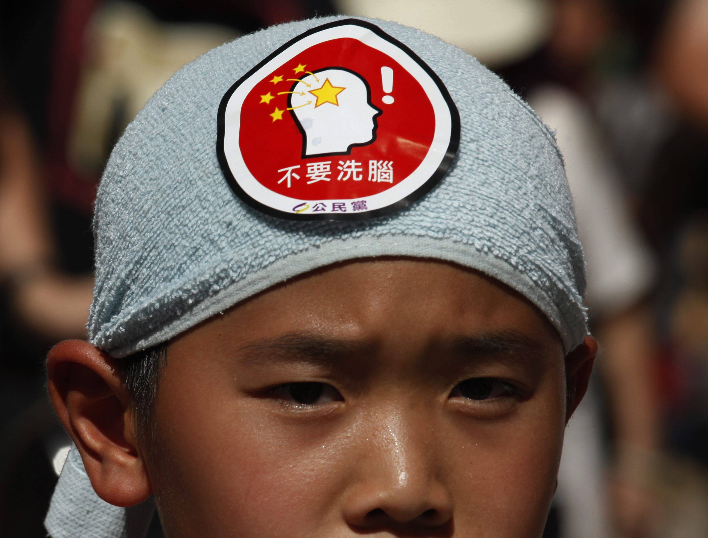 A child, bearing a sticker, protest against a Chinese patriotic education course in Hong Kong