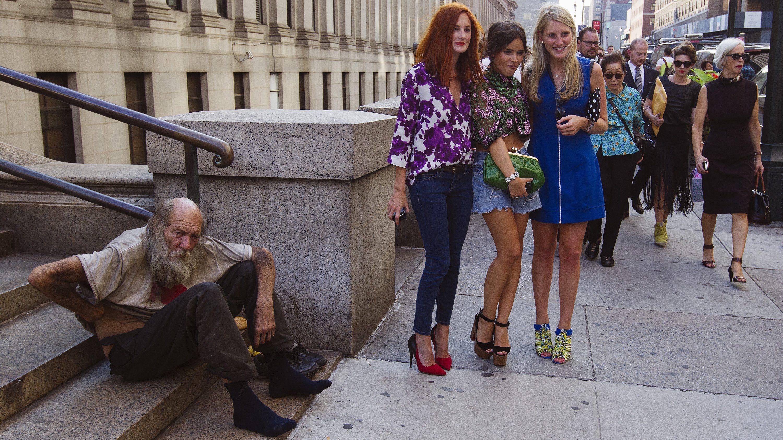 Fashionistas pose next to a homeless man