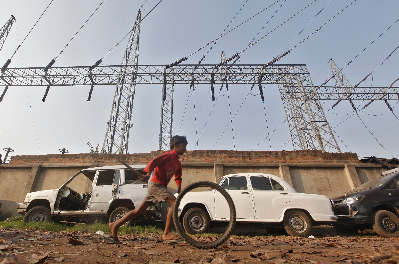 A boy plays with a tyre in front of electric pylons installed at a power house in Kolkata February 21, 2013. India's Finance Minister Palaniappan Chidambaram will present one of the most highly anticipated budgets of recent years, a blueprint for austerity that forms the centrepiece of India's efforts to stave off a ratings downgrade. Investors will watch closely to see whether he will fulfil his promise of fiscal prudence.