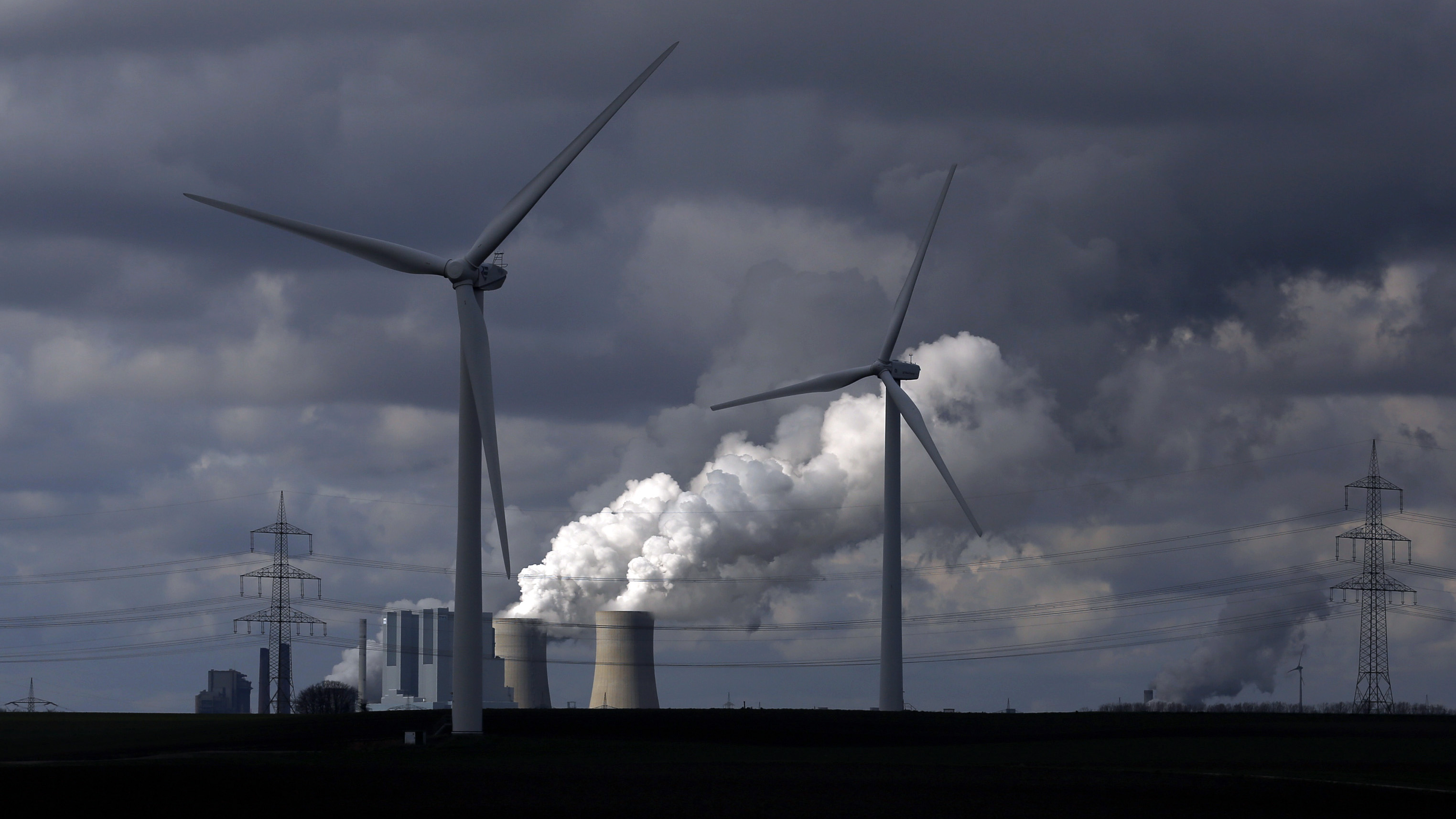 Wind turbines are seen in front of a coal power plant of German utility RWE Power near the western town of Neurath February 28, 2014. Germany's No.2 utility RWE posted a steep net loss for 2013, due to 4.8 billion euros ($6.6 billion) in writedowns mainly on its ailing power plants, which have come under pressure from a massive rise in renewable energy capacity in its home market. Picture taken on February 28. REUTERS/Ina Fassbender  (GERMANY - Tags: BUSINESS ENERGY EMPLOYMENT) - RTR3G0H9