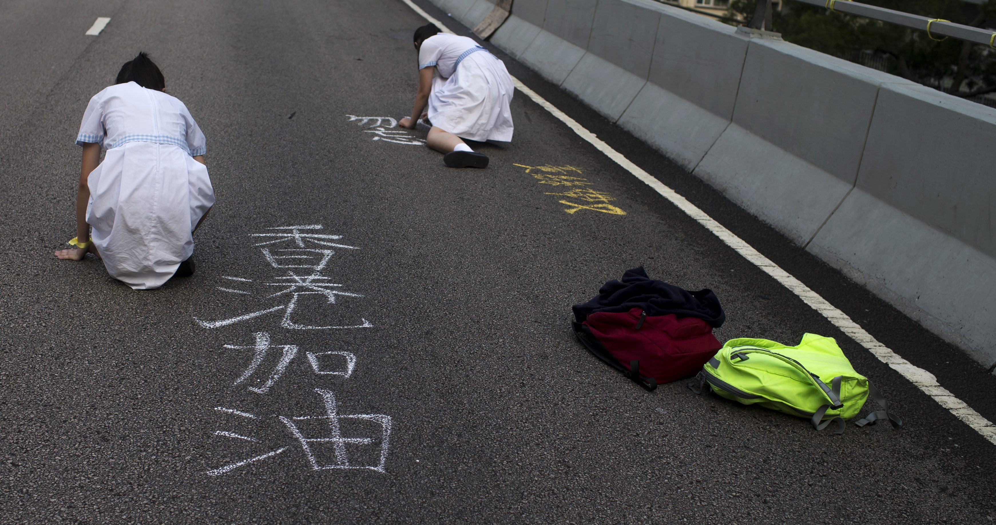 "Secondary school students use chalk to write slogans, reading ""Hong Kong keep going"", along a main road, part of an area blocked off by protesters in Hong Kong"