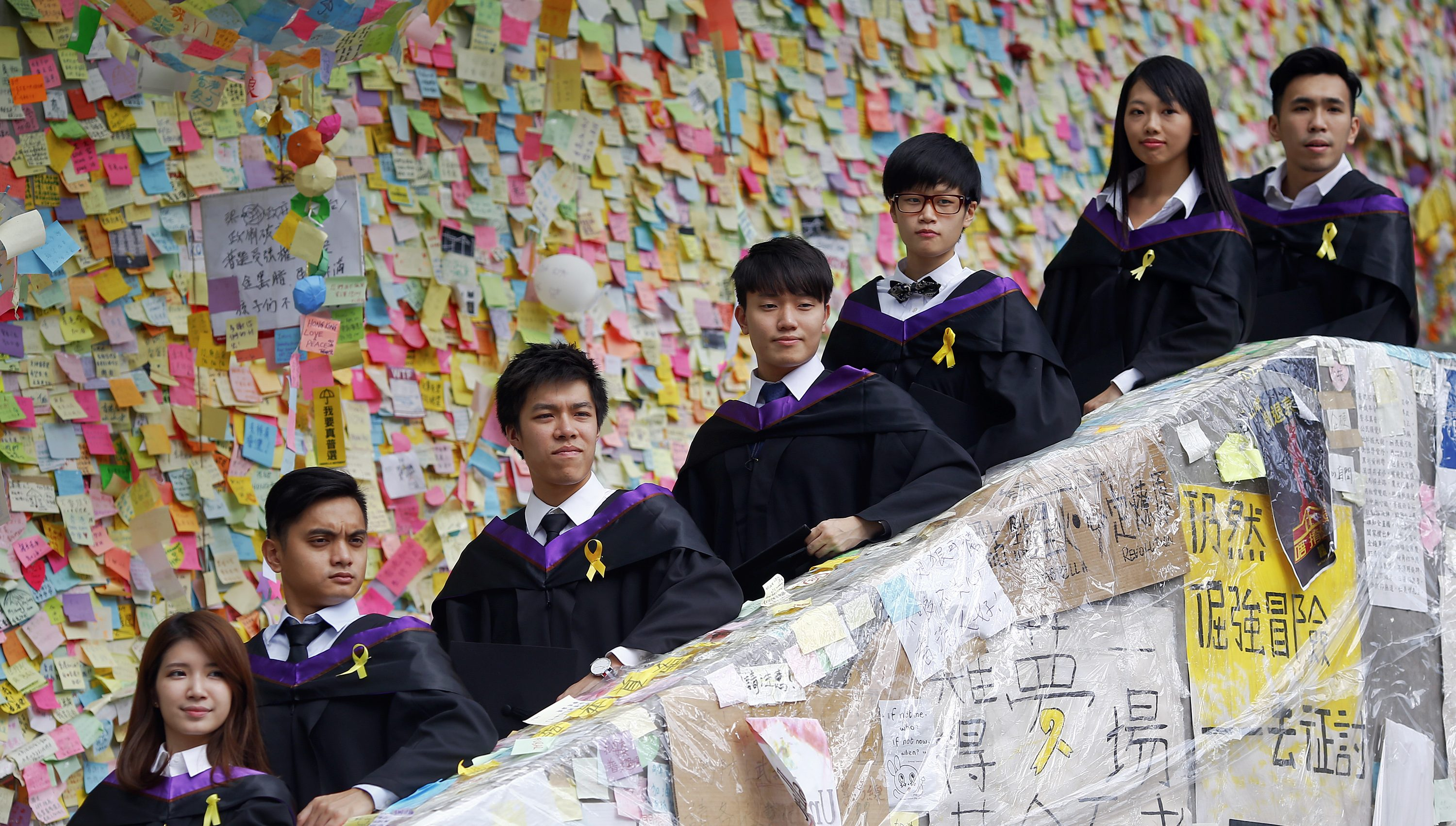 Graduated students of Hong Kong Polytechnic University have their pictures taken in front of a wall with messages of support for the pro-democracy movement in the part of Hong Kong's financial central district protesters are occupying