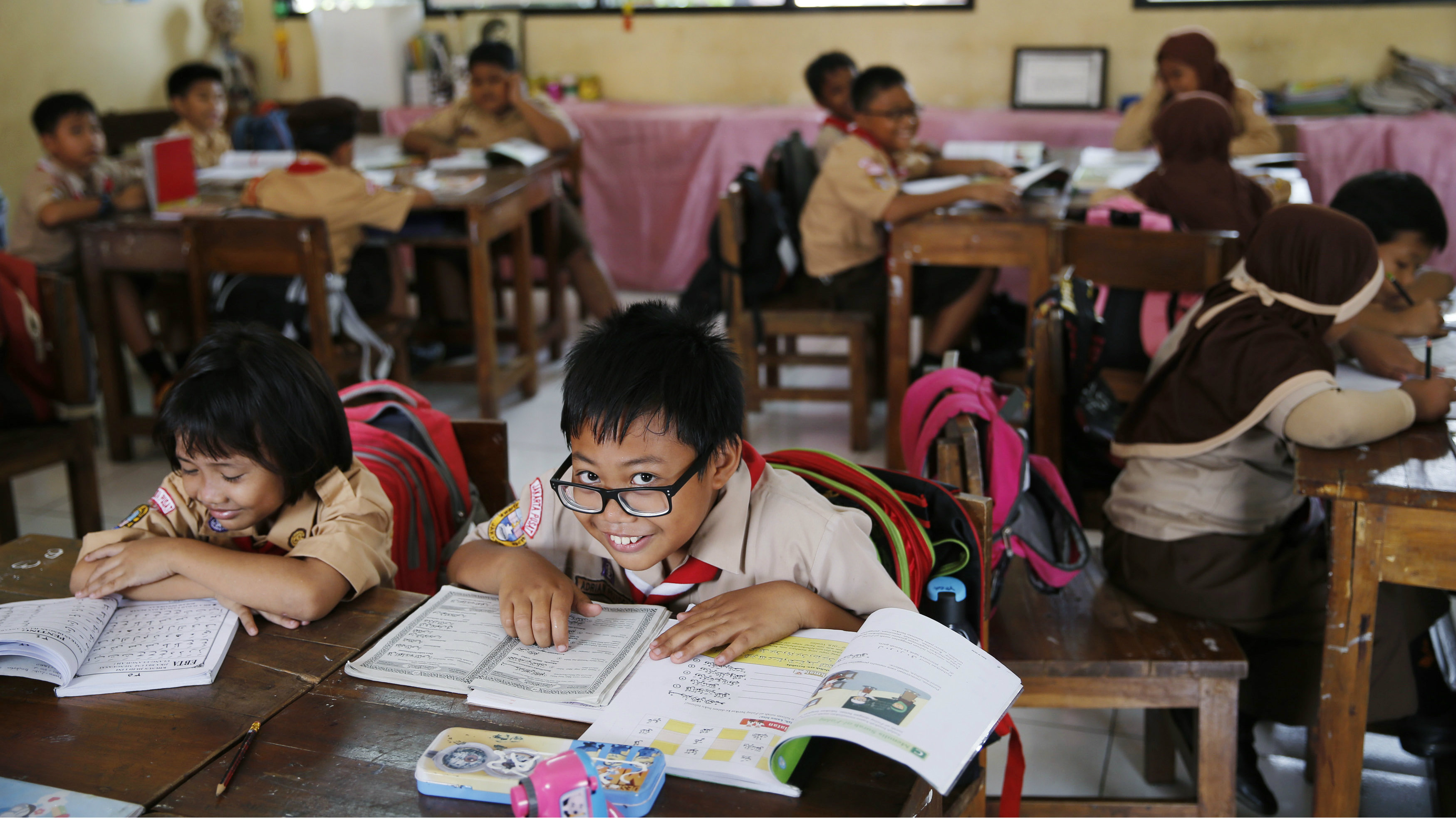Student reacts to the camera as a teacher teaches the 2013 curriculum inside a classroom at Cempaka Putih