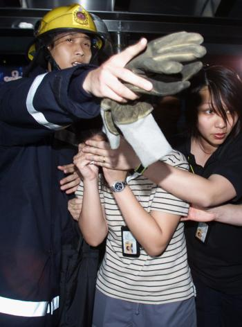 An injured Immigration Department worker is escorted by her colleague and a firefighter after an alleged arsonist attacked the department headquarters in Hong Kong August 2, 2000. More than 40 people were reported injured in the fire, including 16 Immigration staffers and a dozen Chinese migrants.