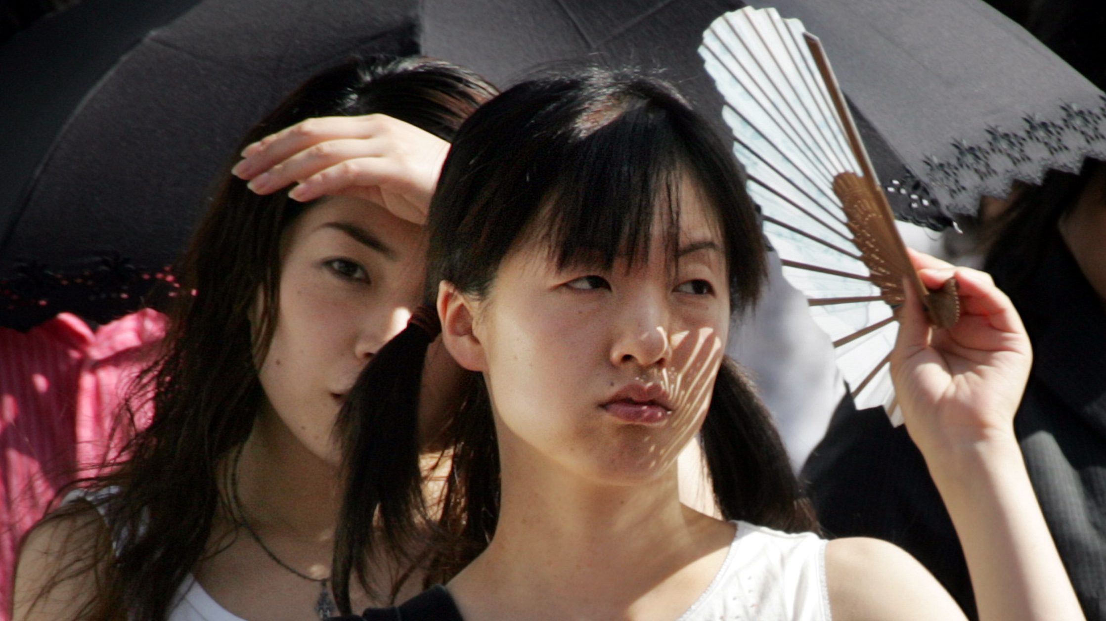 Japanese women shield themselves from the sun on a Tokyo street