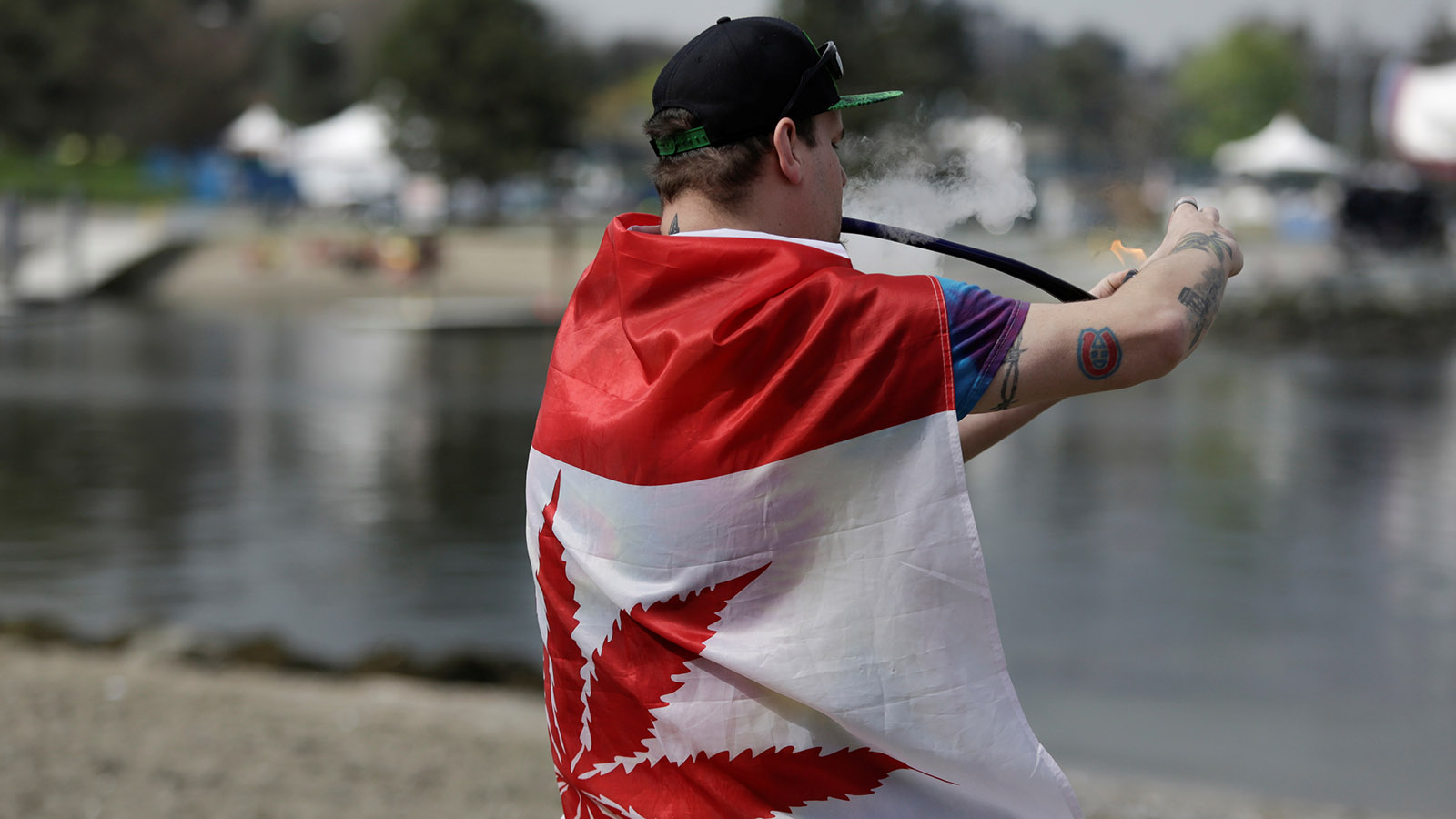 Kevin Lachapelle, 31, of Nanaimo is draped in a pot-leaf flag as he smokes from a pipe at the annual 4/20 marijuana event at Sunset Beach in Vancouver