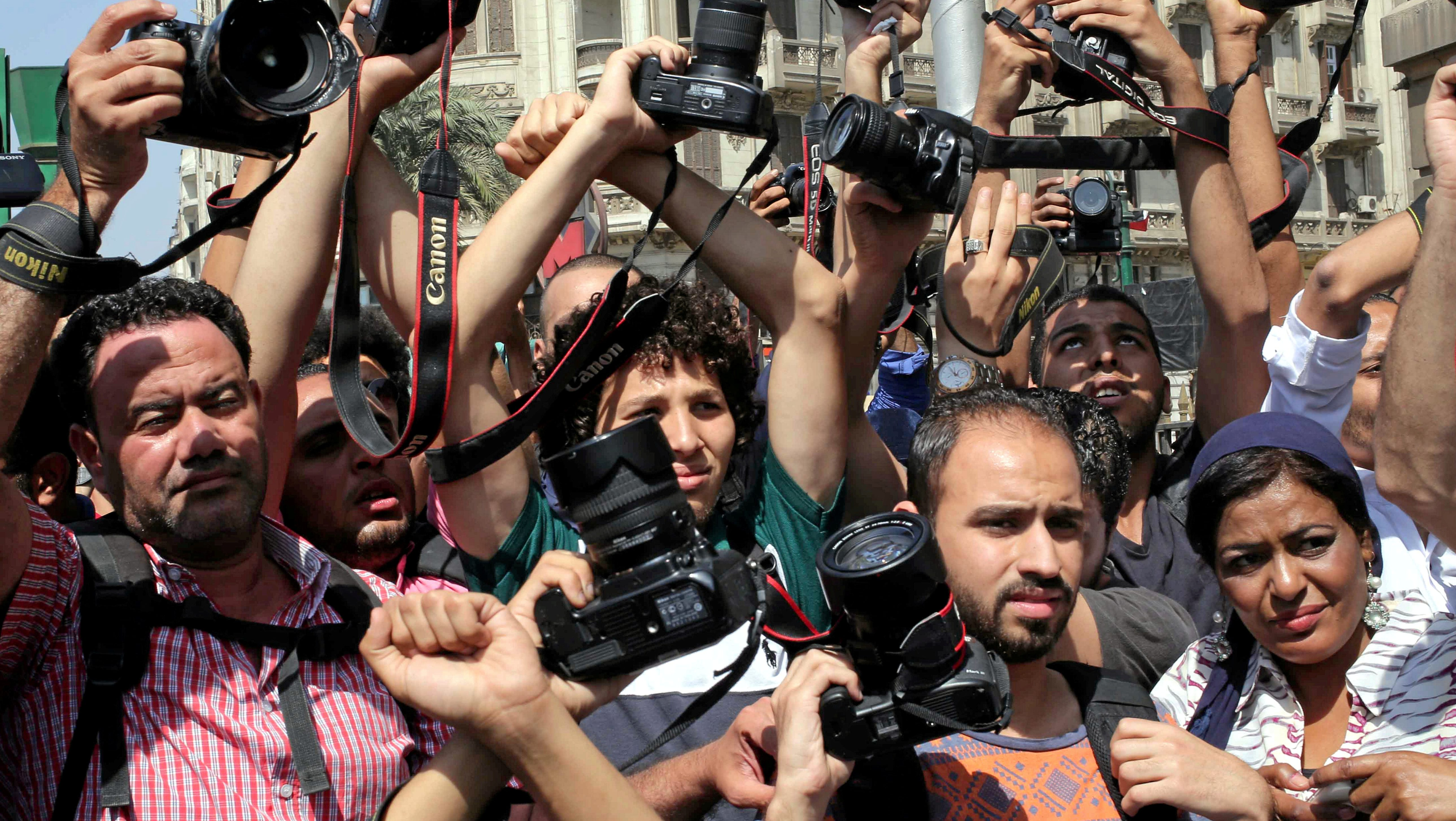 FILE PHOTO: Egyptian journalists hold up their cameras outside the Egyptian Press Syndicate in downtown Cairo, Egypt April 28, 2016.