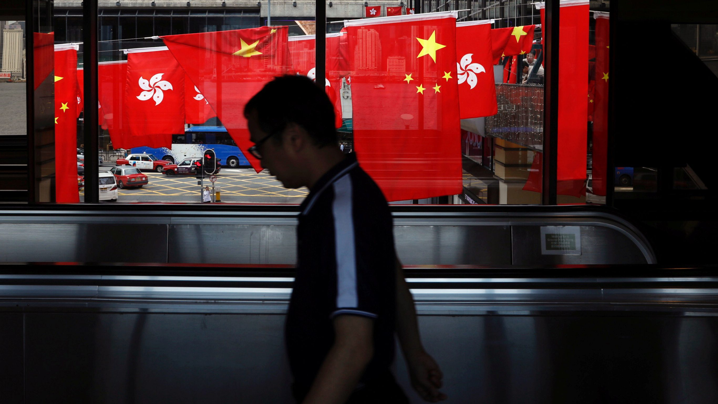 A man walks past Chinese and Hong Kong flags ahead of 20th anniversary of the handover from Britain to China
