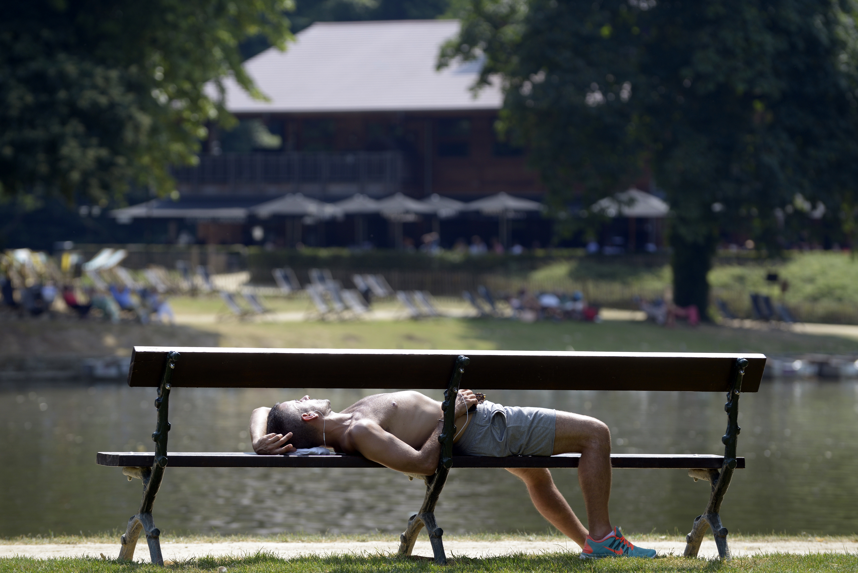 A man sleeps on a bench in a park during a heat wave in Brussels, July 23, 2013.