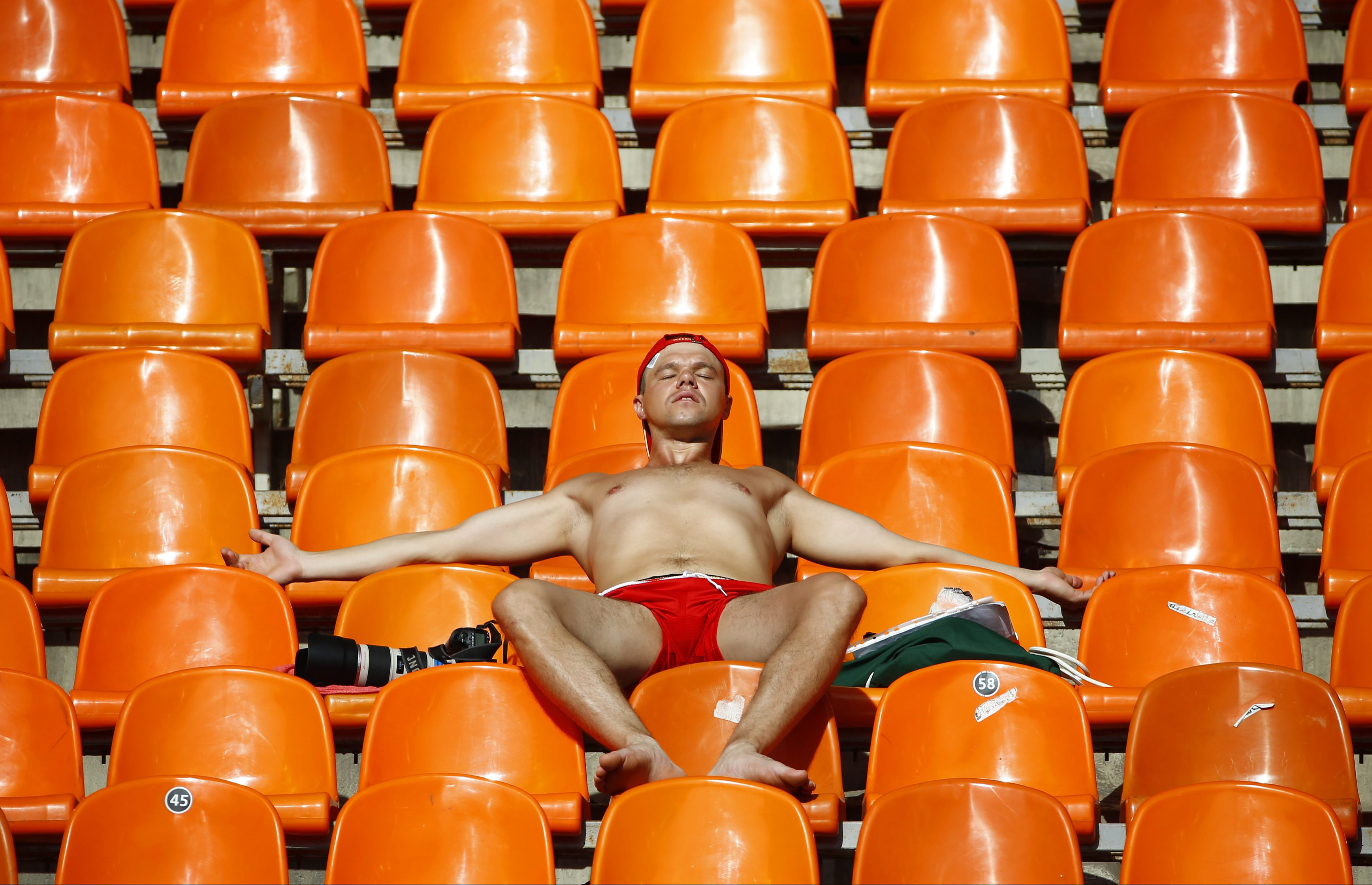 A spectator tans himself in the sun during the morning session of the IAAF World Athletics Championships at the Luzhniki stadium in Moscow August 13, 2013.