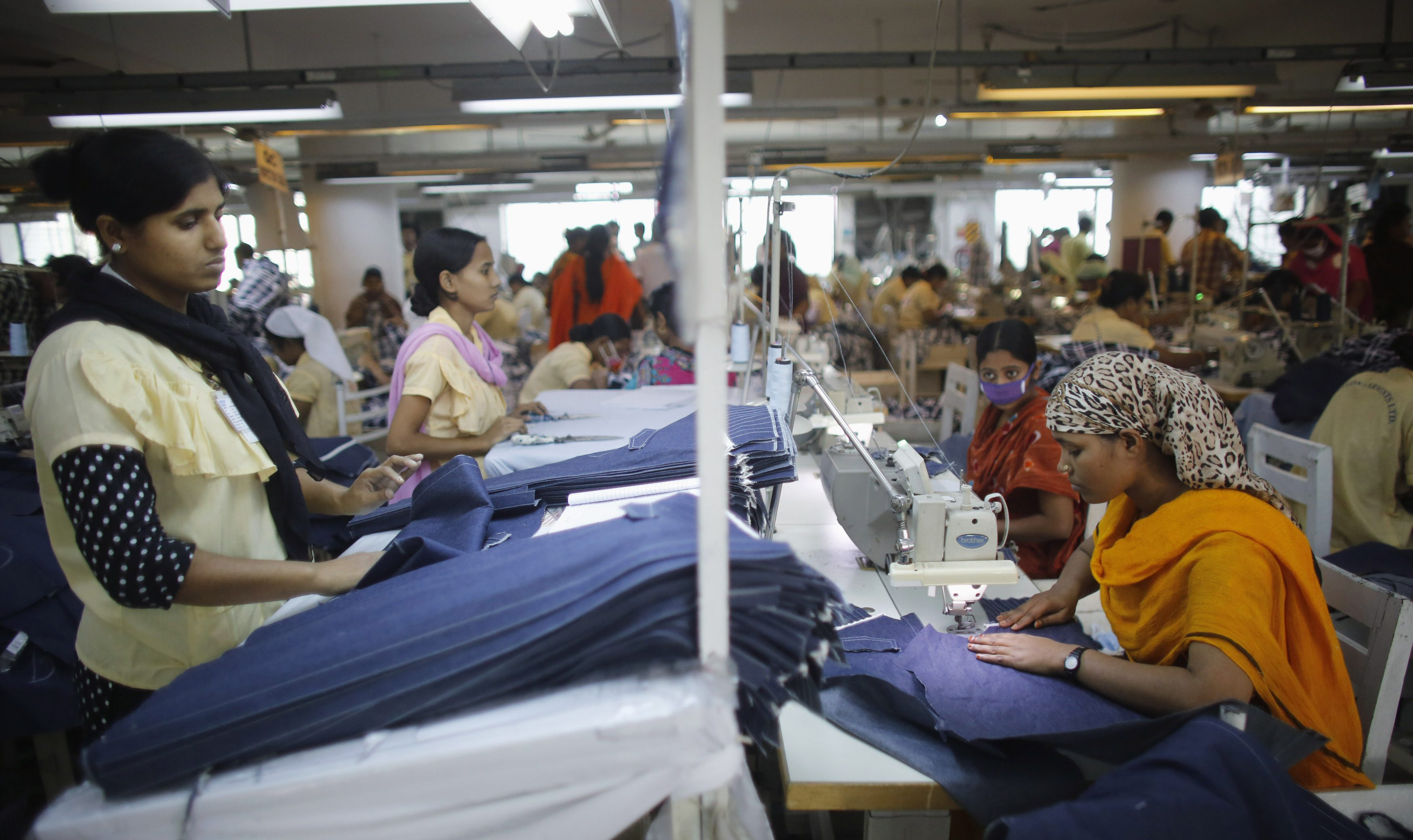 Employees work in a factory of Babylon Garments in Dhaka January 3, 2014. On the outskirts of Dhaka, Babylon Garments has shortened work shifts to eight hours from the usual 10 and plans to shutter production lines as months of election-related violence disrupts transport and prompts global retailers to curb orders. Picture taken January 3, 2014. To match BANGLADESH-GARMENTS/ REUTERS/Andrew Biraj (BANGLADESH - Tags: BUSINESS EMPLOYMENT TEXTILE) - RTX175UR